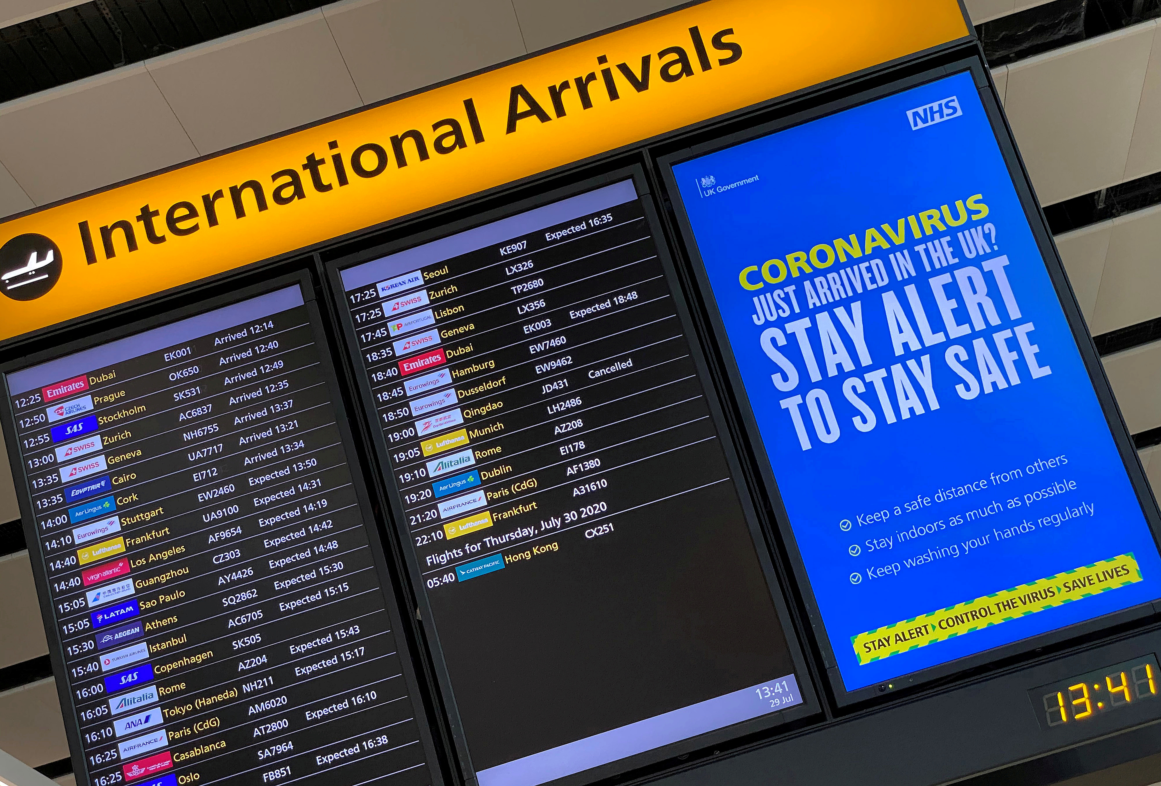 A public health campaign message is displayed on an arrivals information board at Heathrow Airport, following the outbreak of the coronavirus disease (COVID-19), London, Britain, July 29, 2020. REUTERS/Toby Melville//File Photo