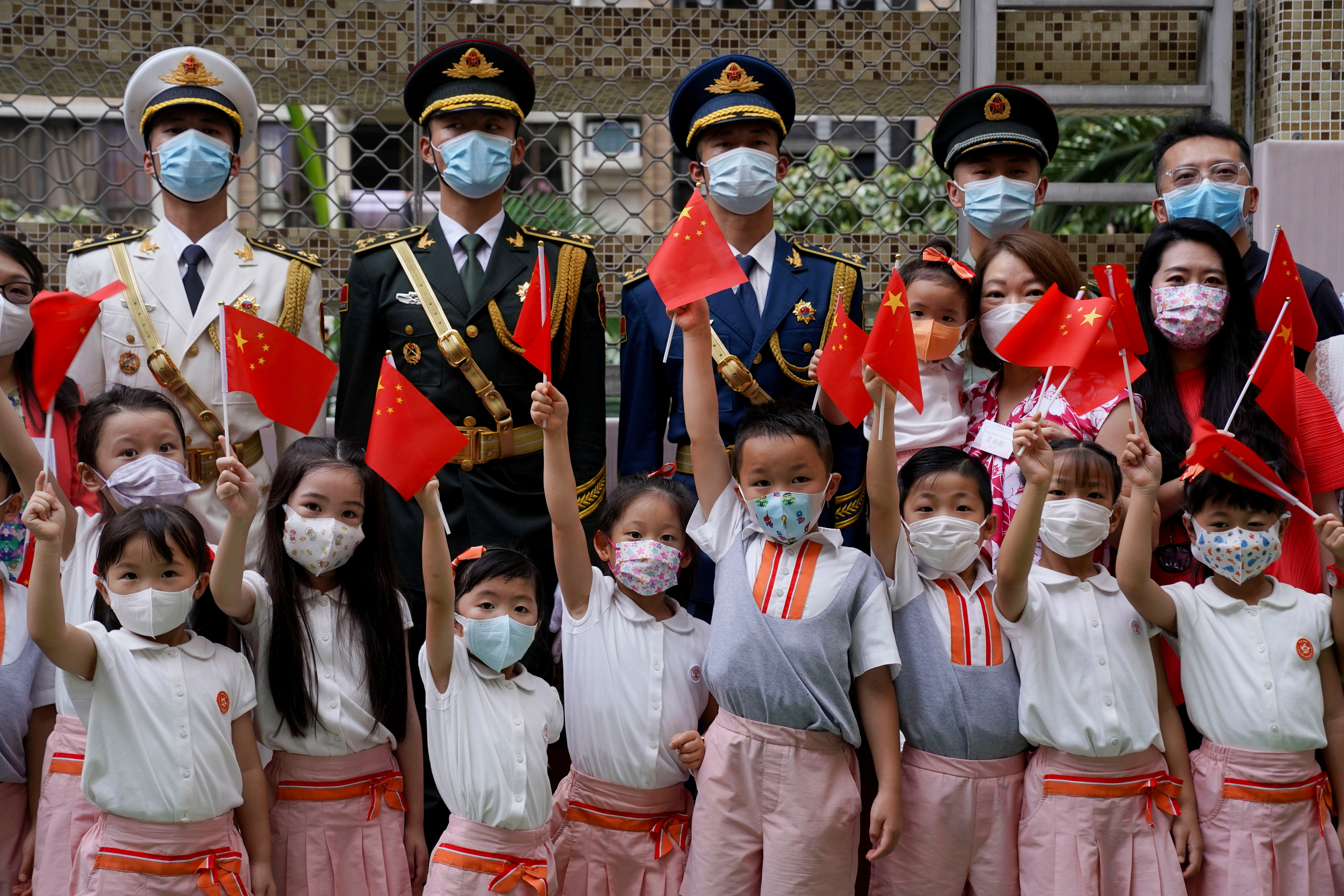 Students take a picture with the People's Liberation Army during morning assembly at a secondary school, marking the 24th anniversary of the former British colony's return to Chinese rule, on the 100th founding anniversary of the Communist Party of China, in Hong Kong, China July 1, 2021. REUTERS/Lam Yik