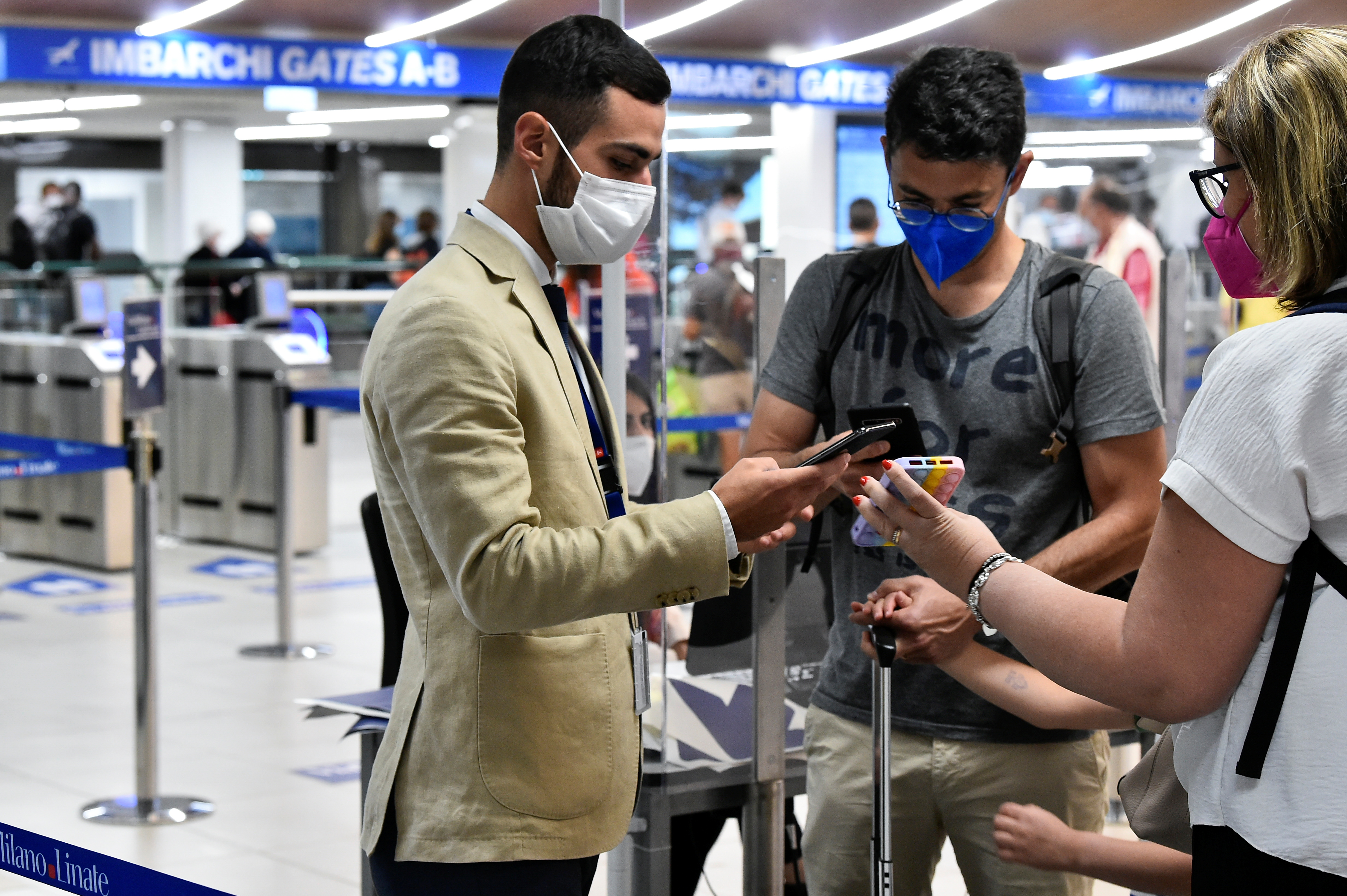 People show their digital COVID-19 certificates at Linate Airport in Milan, Italy, September 1, 2021. REUTERS/Flavio Lo Scalzo