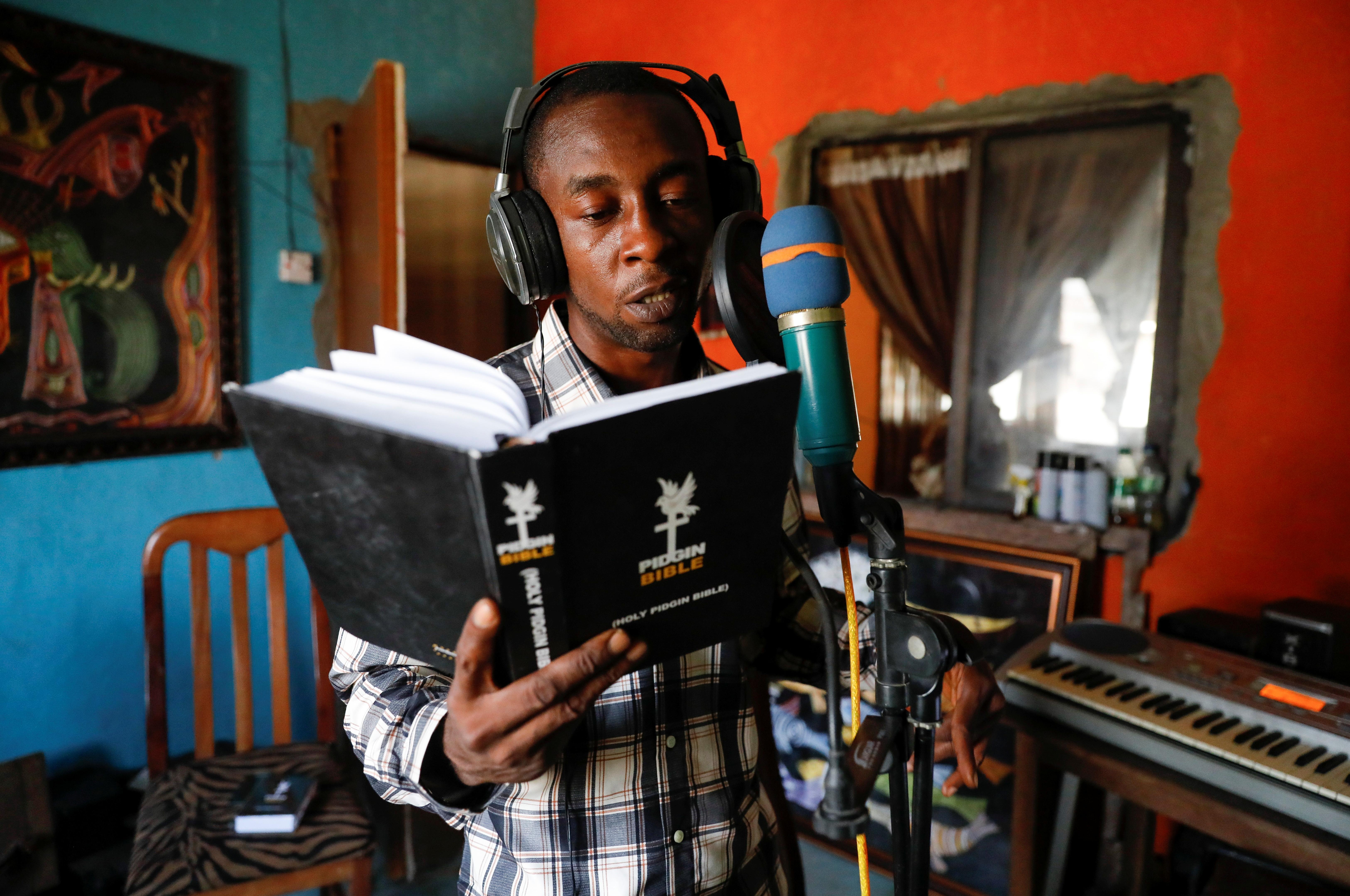 Salem Egoh, translator of the Bible into Nigerian Pidgin, reads as he records the audio version at his studio in Lekki, Lagos, Nigeria June 25, 2021. REUTERS/Temilade Adelaja