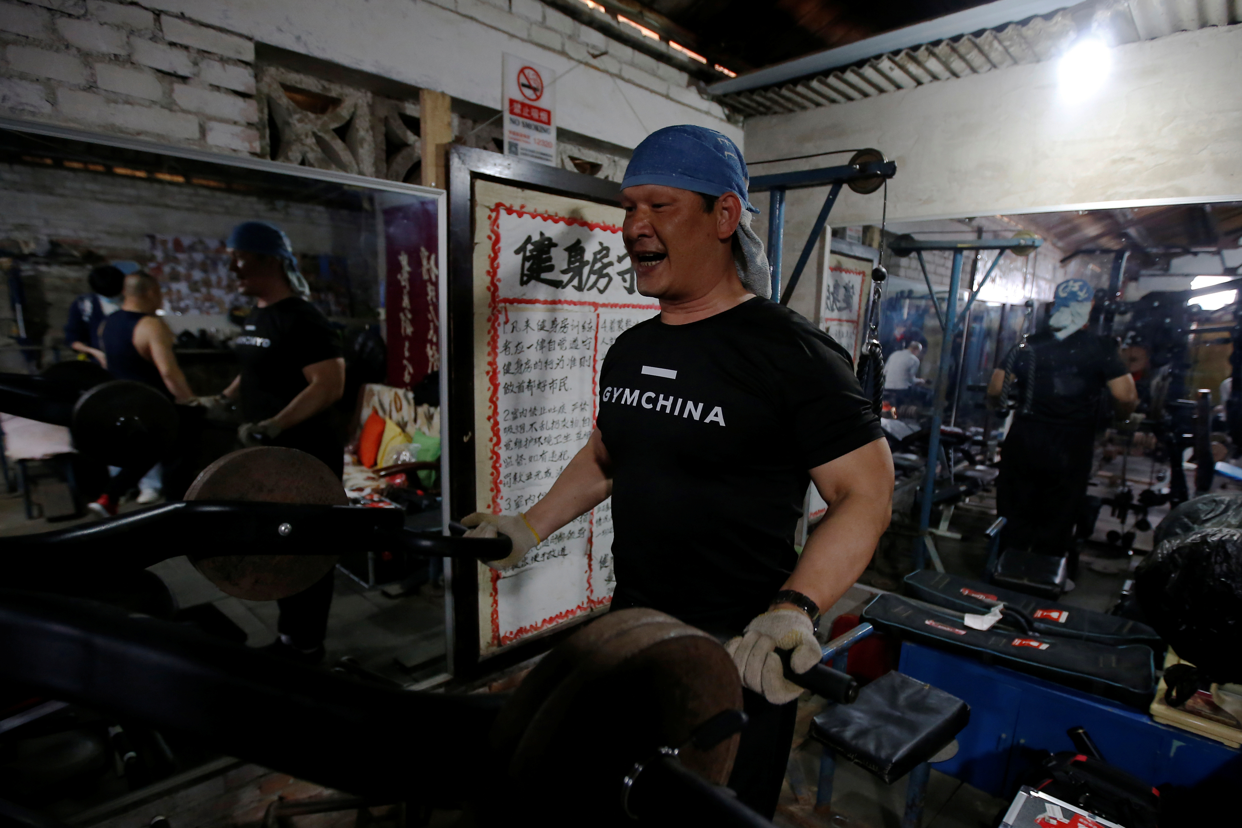 Liu Hongtao, 53, works out at a gym which has been turned from a bicycle shed inside a residential compound in the southwest of Beijing, China April 8, 2021. REUTERS/Tingshu Wang