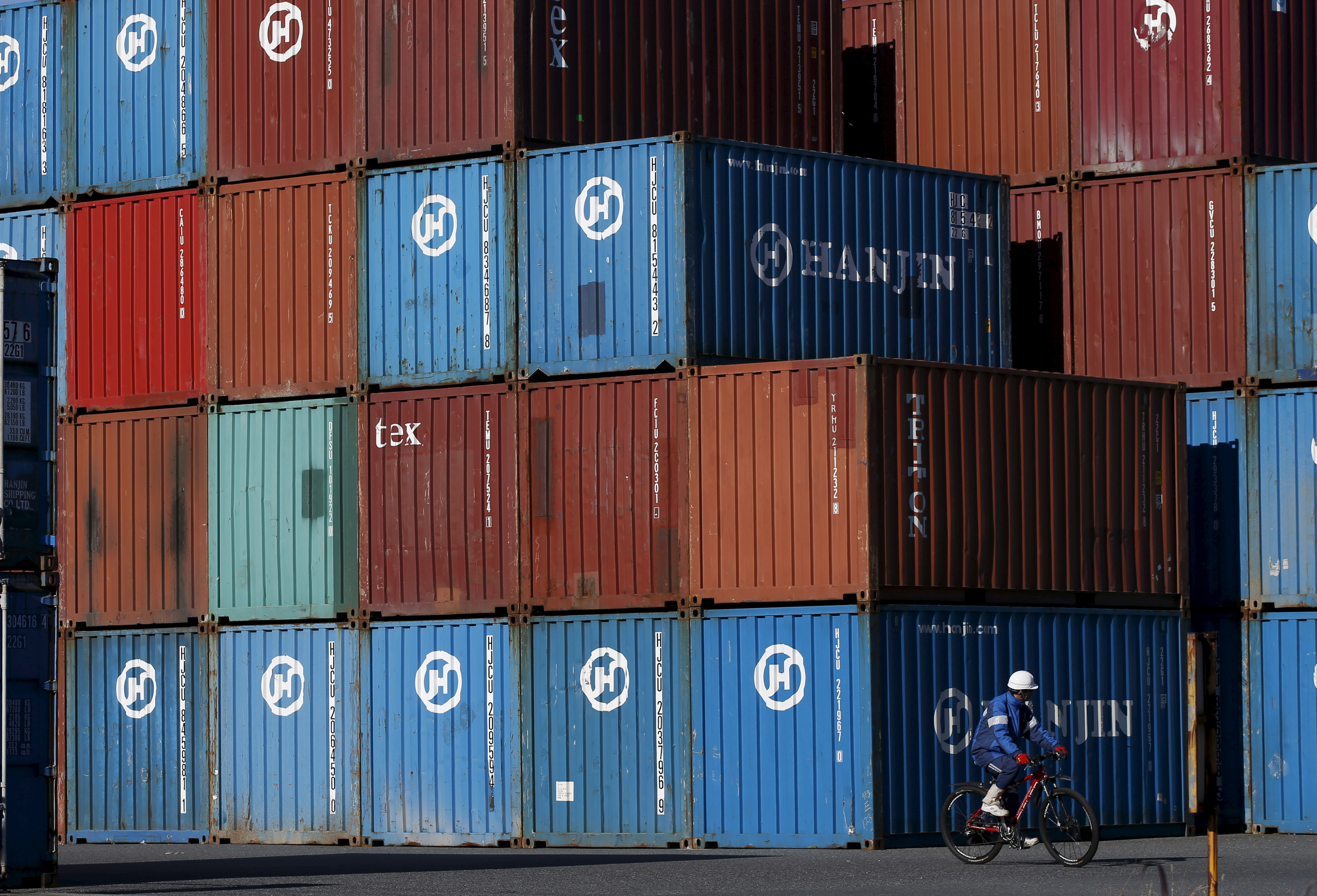 A worker rides a bicycle in a container area at a port in Tokyo, Japan January 25, 2016. REUTERS/Toru Hanai