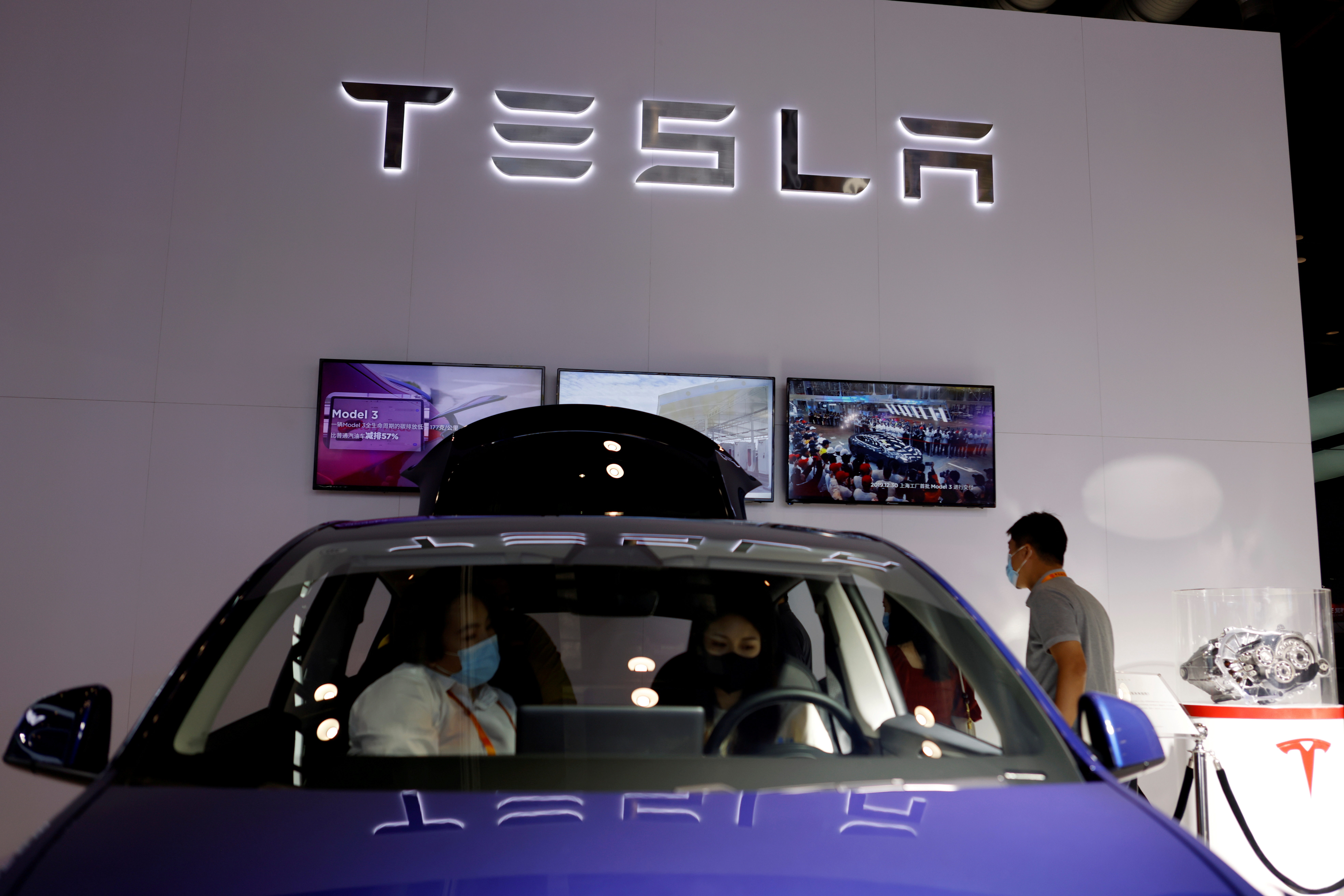 People check a Tesla Model Y electric vehicle (EV) displayed at its booth during the 2021 China International Fair for Trade in Services (CIFTIS) in Beijing, China September 4, 2021.