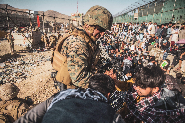 A U.S. Marine assists at an Evacuation Control Check Point (ECC) during an evacuation at Hamid Karzai International Airport, Kabul, Afghanistan, August 26, 2021. U.S. Marine Corps/Staff Sgt. Victor Mancilla/Handout via REUTERS.