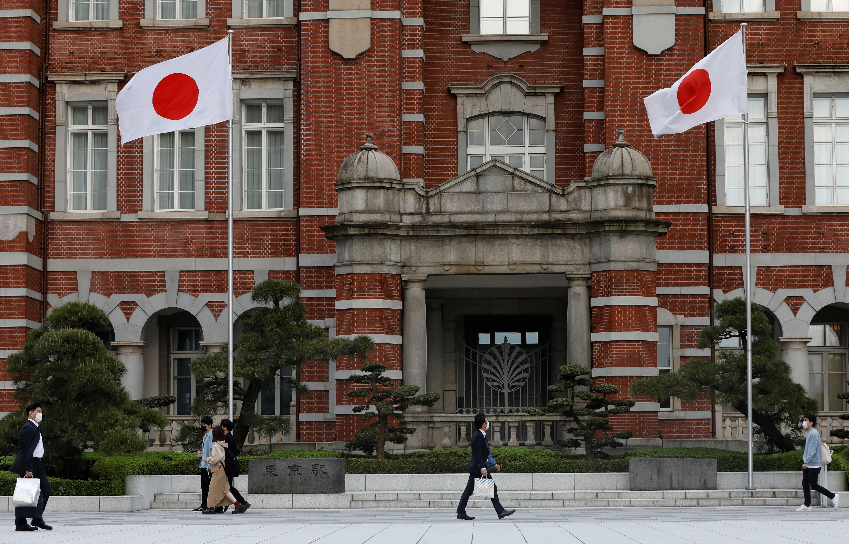 Pedestrians wearing protective face masks amid the coronavirus disease (COVID-19) pandemic walk past Japanese national flags in Tokyo, Japan, April 8, 2021. REUTERS/Kim Kyung-Hoon