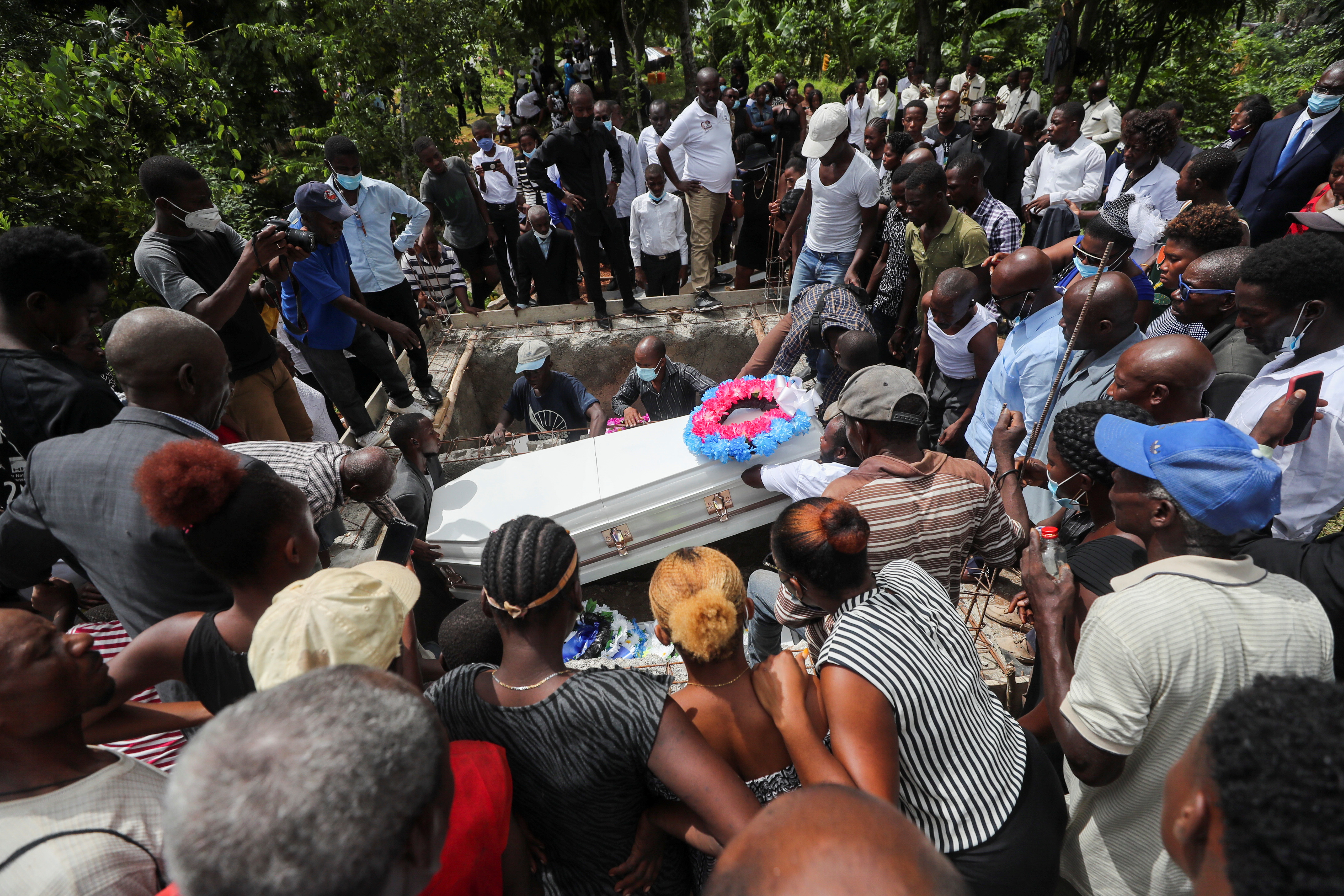 People take part in a funeral after the earthquake that took place on August 14th, in Marceline near Les Cayes, Haiti August 21, 2021. REUTERS/Henry Romero