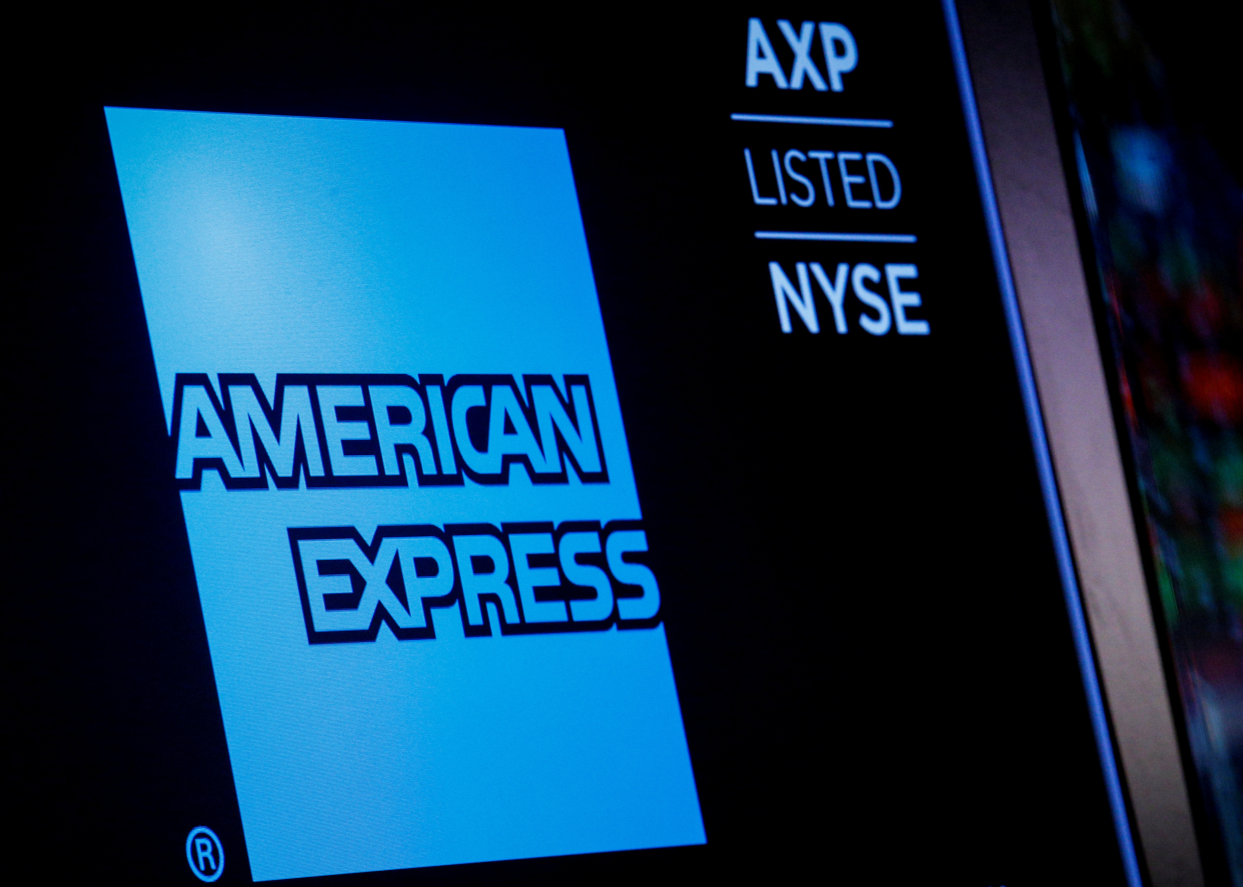 American Express logo and trading symbol are displayed on a screen at the New York Stock Exchange (NYSE) in New York, U.S., December 6, 2017. REUTERS/Brendan McDermid/File Photo