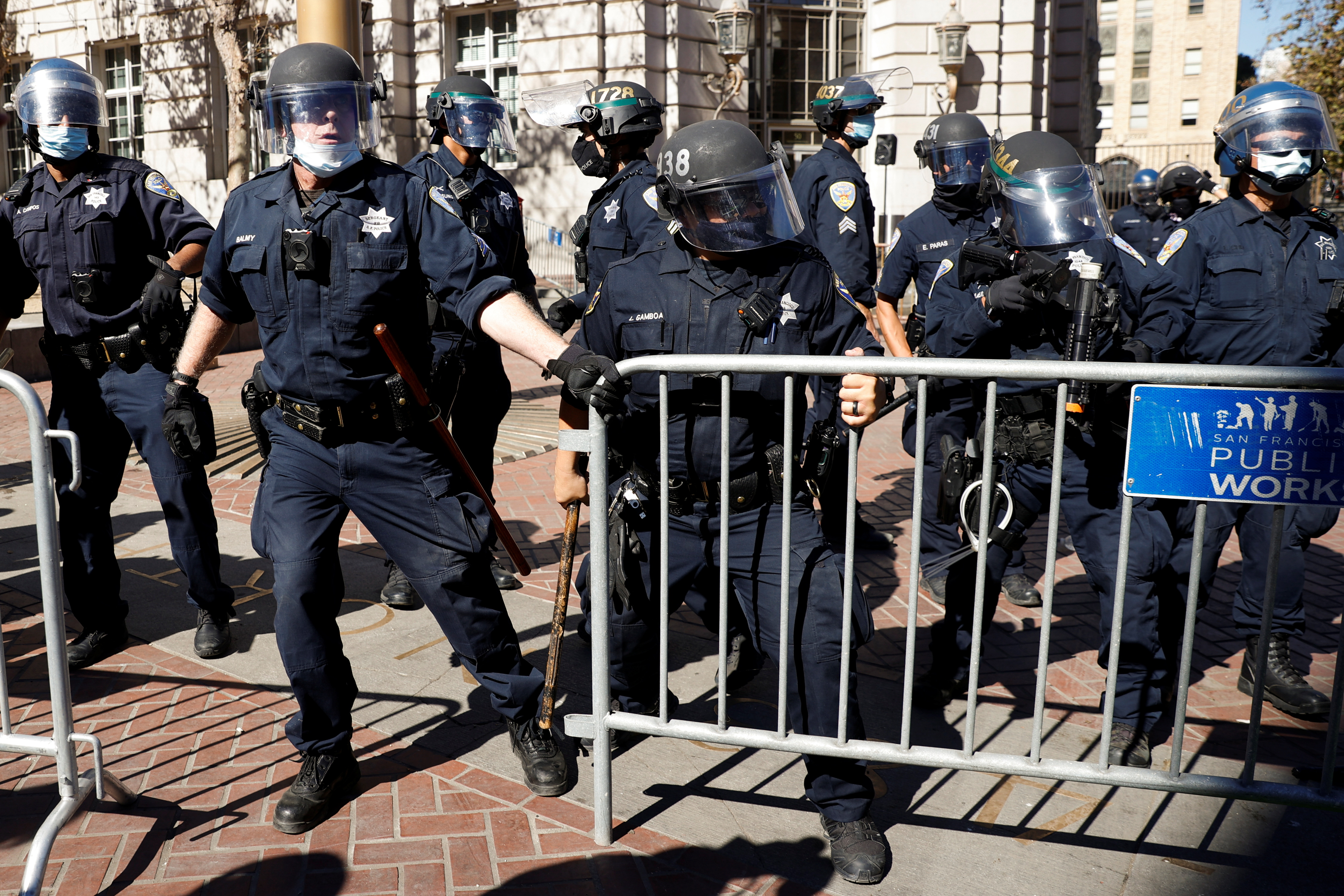 Officers with the San Francisco Police Department work to close a barricade during a rally and a counter-demonstration at the United Nations Plaza in San Francisco, California, U.S. October 17, 2020. REUTERS/Stephen Lam