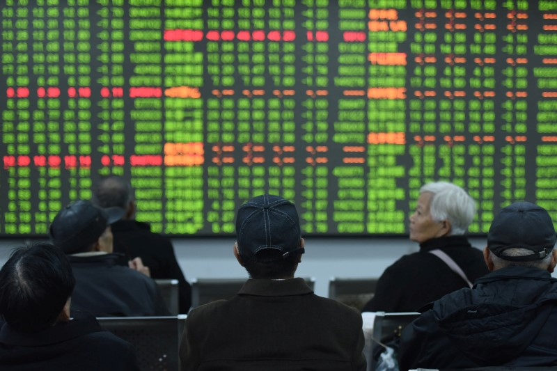 Investors sit in front of a board showing stock information at a brokerage house on the first day of trade in China since the Lunar New Year, in Hangzhou, Zhejiang province, China February 3, 2020. China Daily via REUTERS/File Photo
