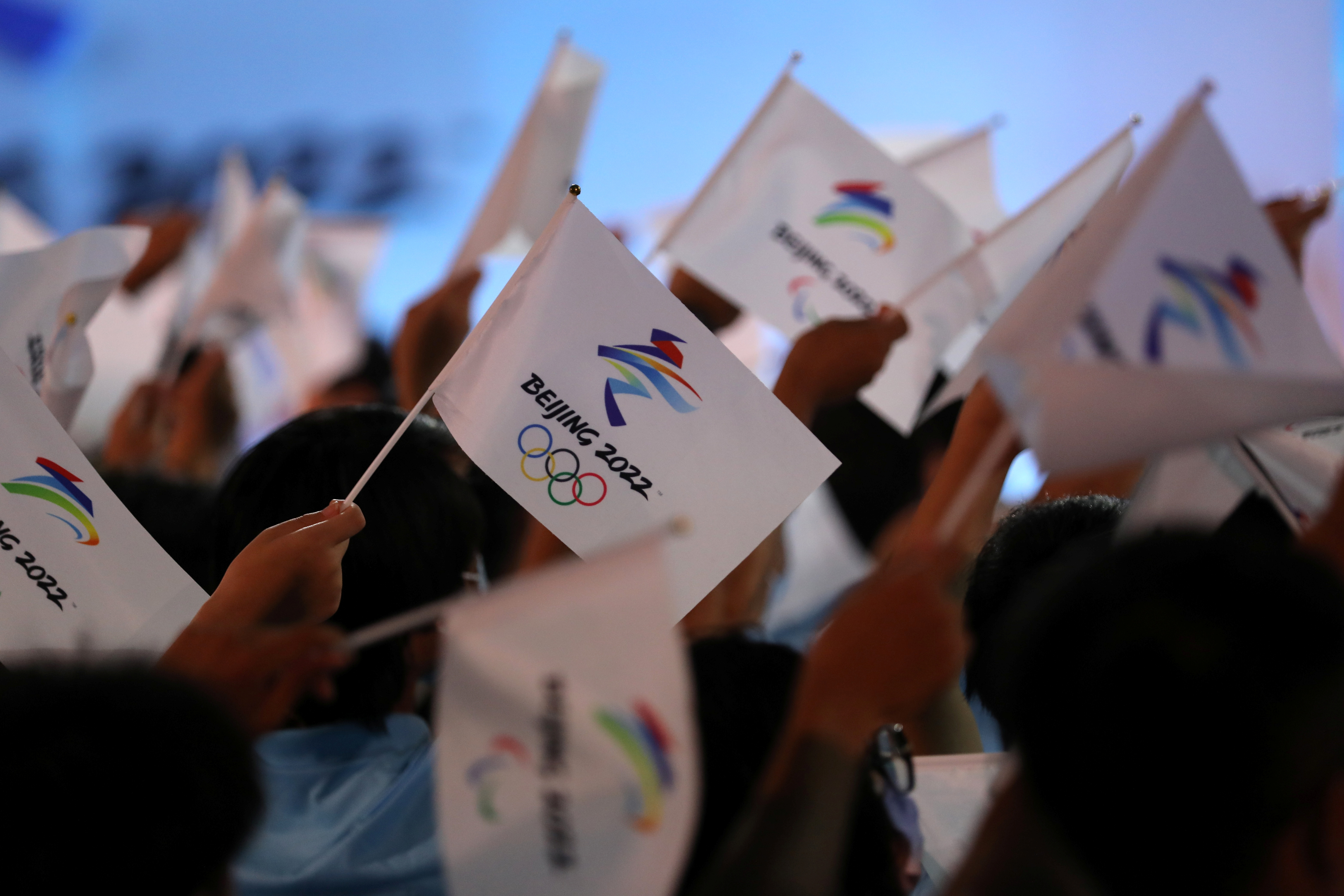 Attendees wave flags with the emblem of the Beijing 2022 Winter Olympic Games at a ceremony unveiling the slogan, in Beijing, China September 17, 2021. REUTERS/Tingshu Wang