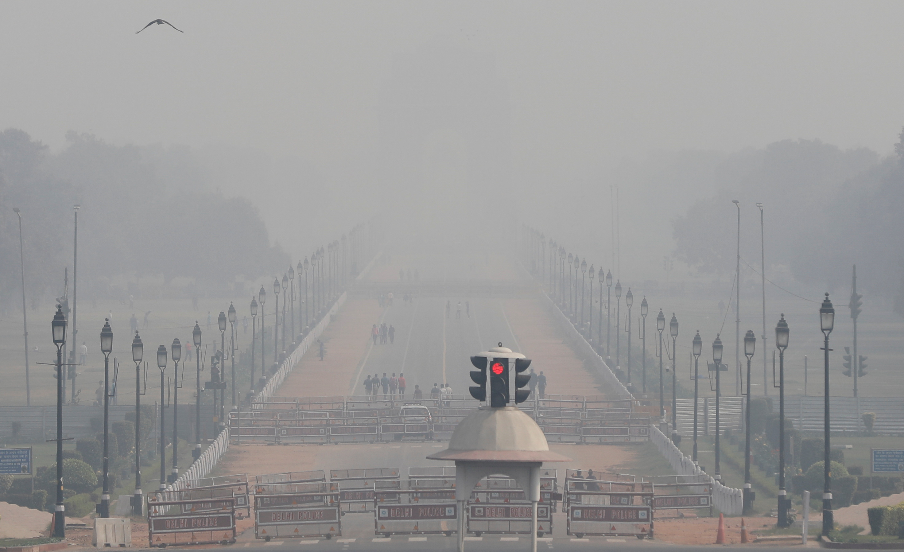 People walk near India Gate on a smoggy afternoon in New Delhi, India, November 15, 2020. REUTERS/Adnan Abidi