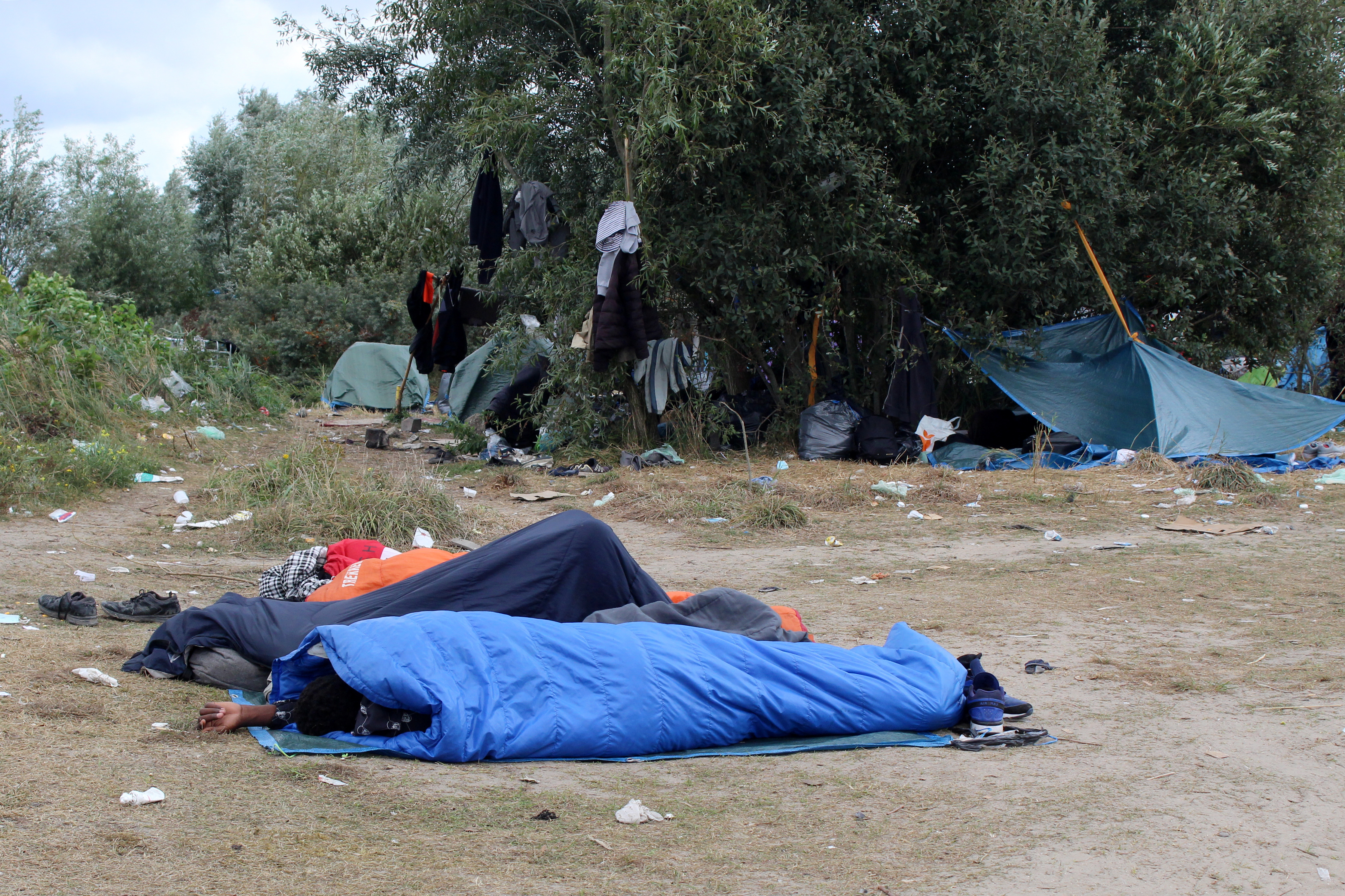 Migrants sleep in sleeping bags at a makeshift migrant camp near the hospital in Calais, France, September 10, 2021. REUTERS/Forrest Crellin