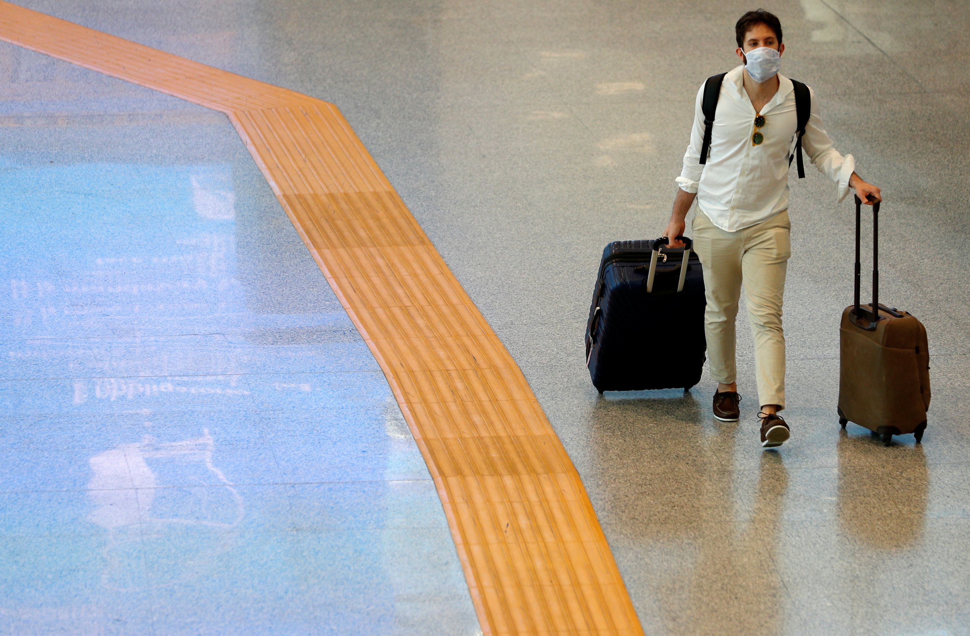 A passenger wearing a protective face mask walks at Fiumicino Airport in Rome, Italy, May 28, 2020. REUTERS/Guglielmo Mangiapane