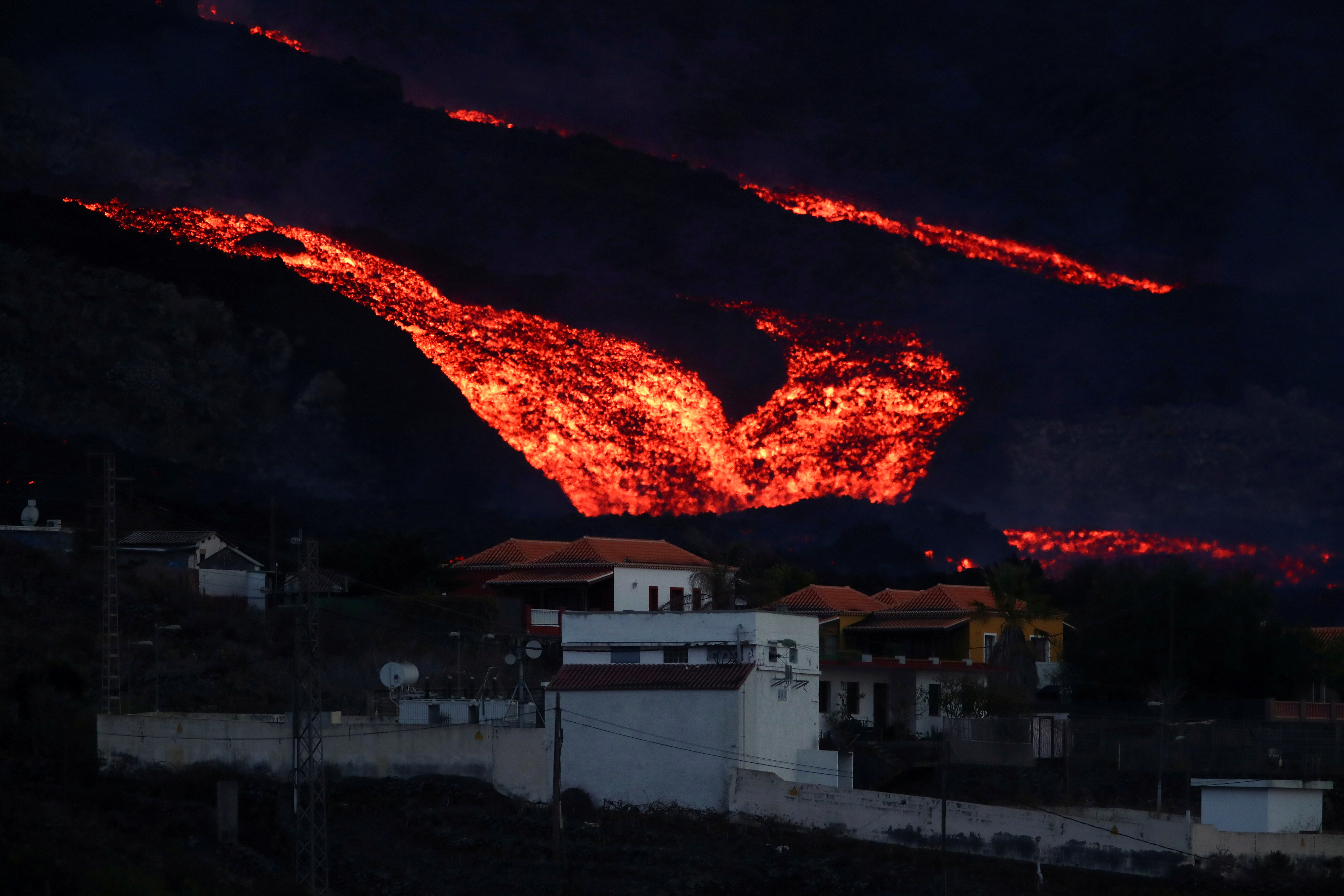 Lava flows down behind houses in Los Llanos as the Cumbre Vieja volcano continues to erupt on the Canary Island of La Palma, as seen from Tajuya, Spain, October 13, 2021. REUTERS/Sergio Perez     TPX IMAGES OF THE DAY