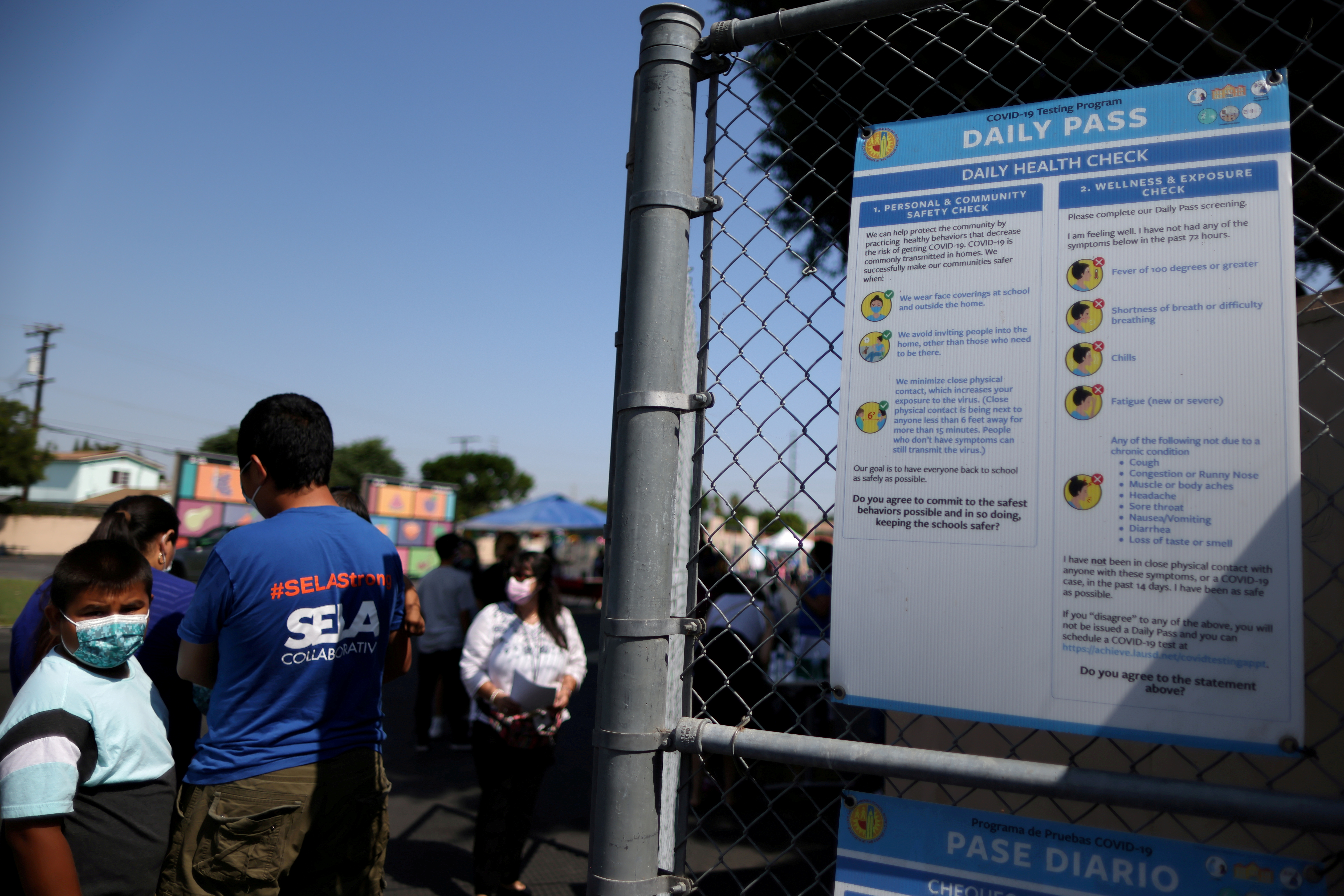 People wait in line at a school for coronavirus disease (COVID-19) testing and vaccines in South Gate, Los Angeles, California, U.S., August 12, 2021. REUTERS/Lucy Nicholson/File Photo