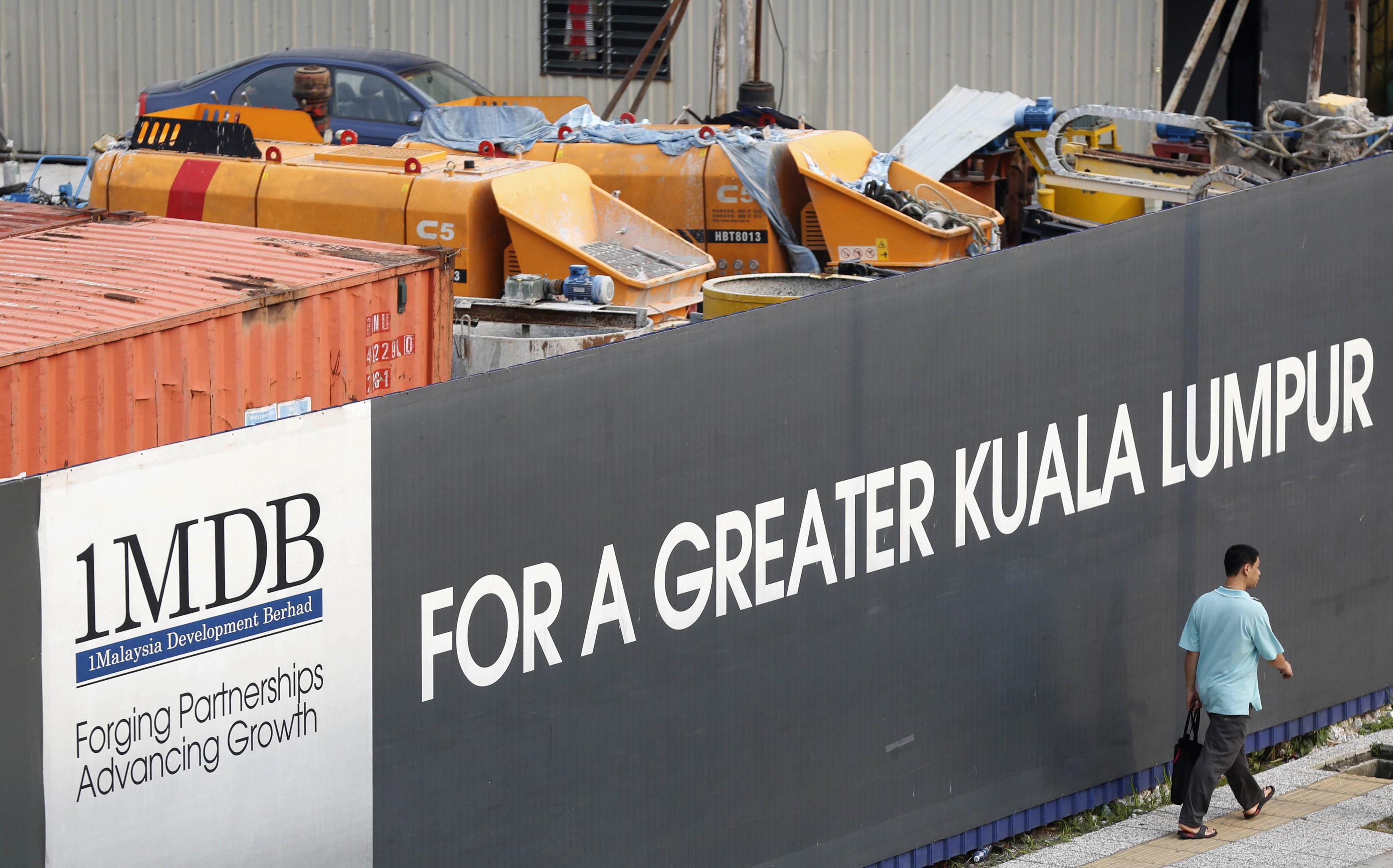 A man walks past a 1 Malaysia Development Berhad (1MDB) billboard at the funds flagship Tun Razak Exchange development in Kuala Lumpur, March 1, 2015. REUTERS/Olivia Harris