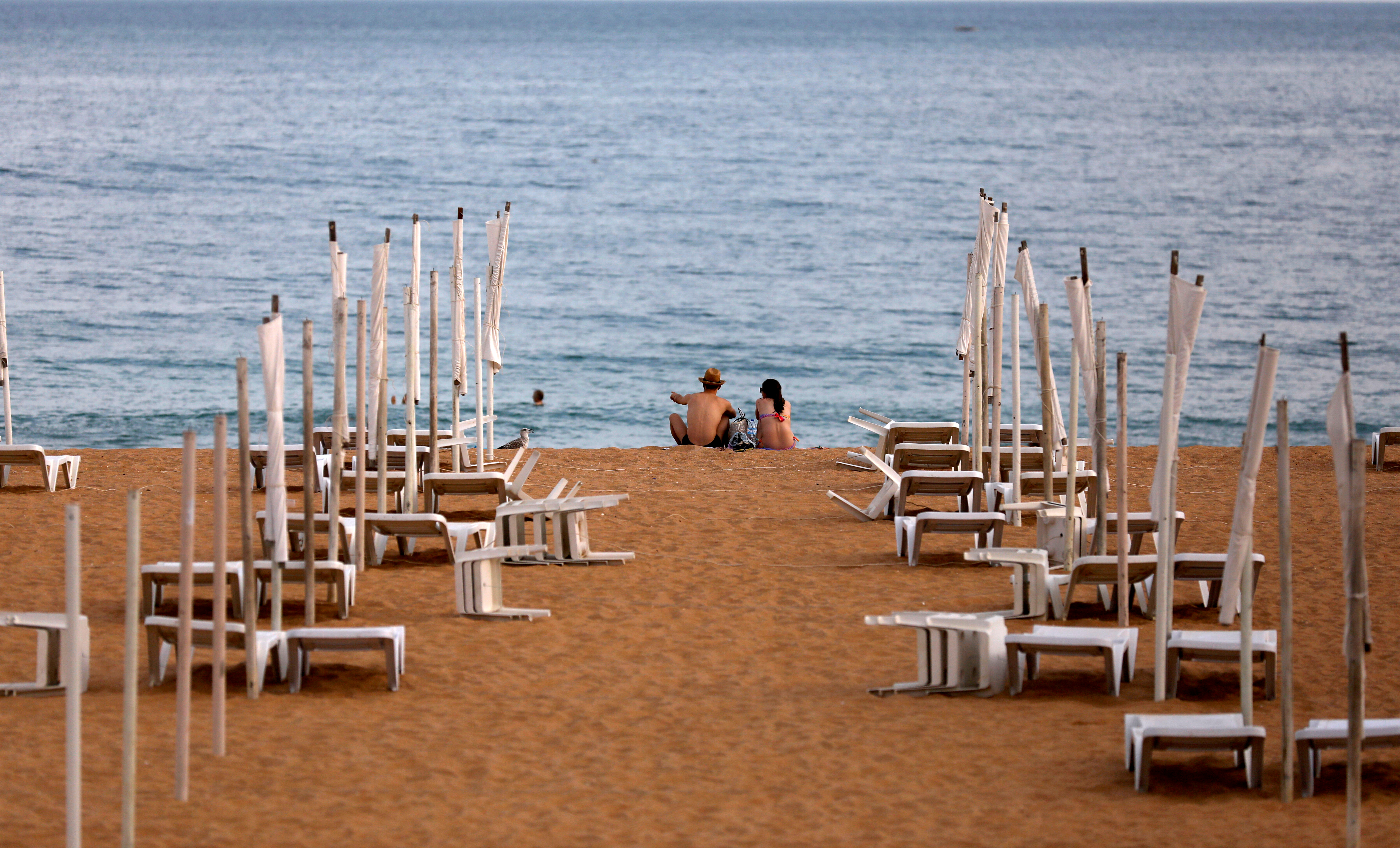 A couple is seen next to rows of empty hammocks during the coronavirus pandemic in Albufeira, Portugal, July 20, 2020. REUTERS/Rafael Marchante/File Photo