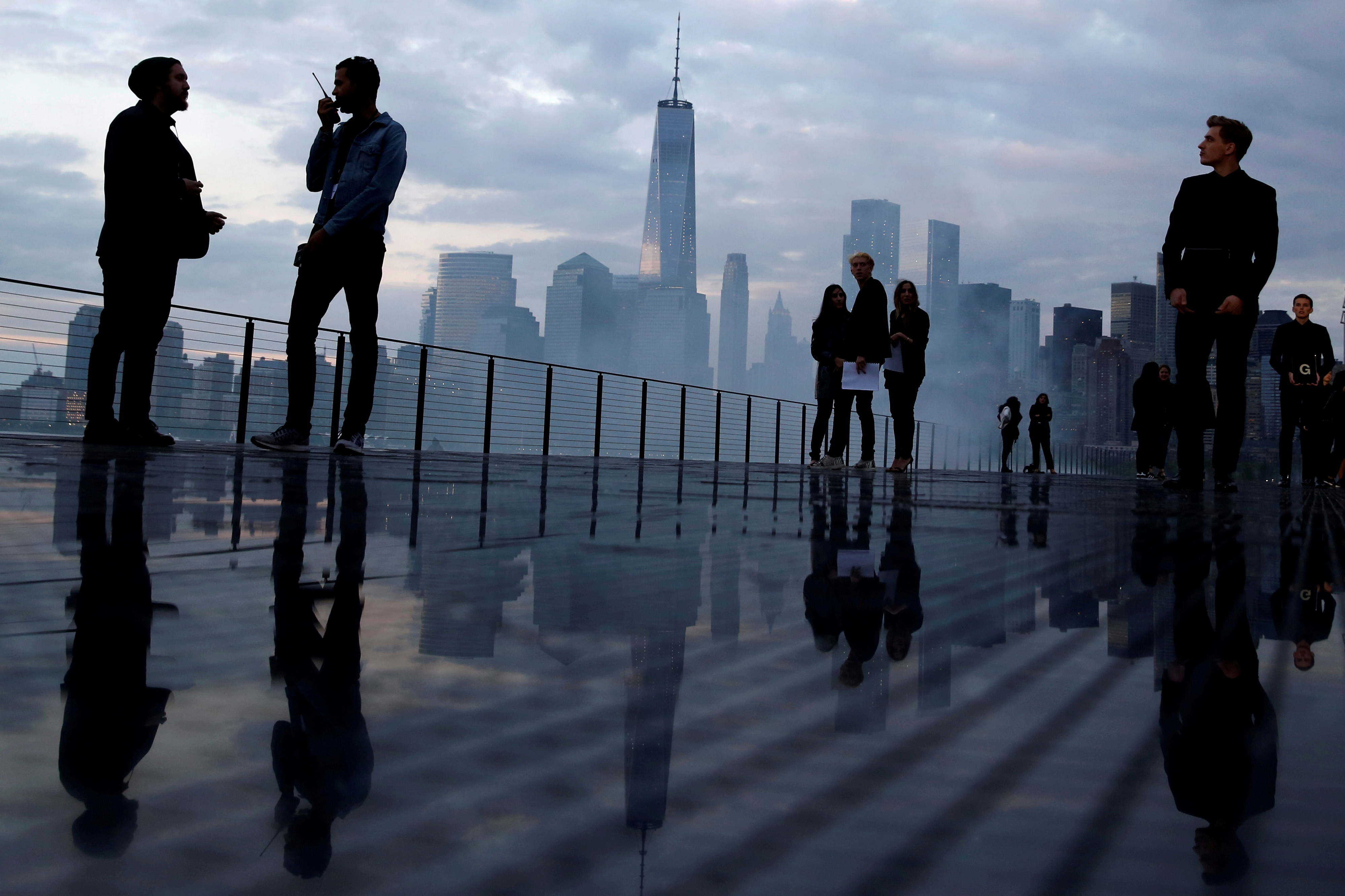 The skyline of downtown Manhattan is seen as people gather on the runway before the Saint Laurent Men's Spring/Summer 2019 collection presentation in Liberty State Park in New Jersey, U.S., June 6, 2018.  REUTERS/Andrew Kelly/File Photo