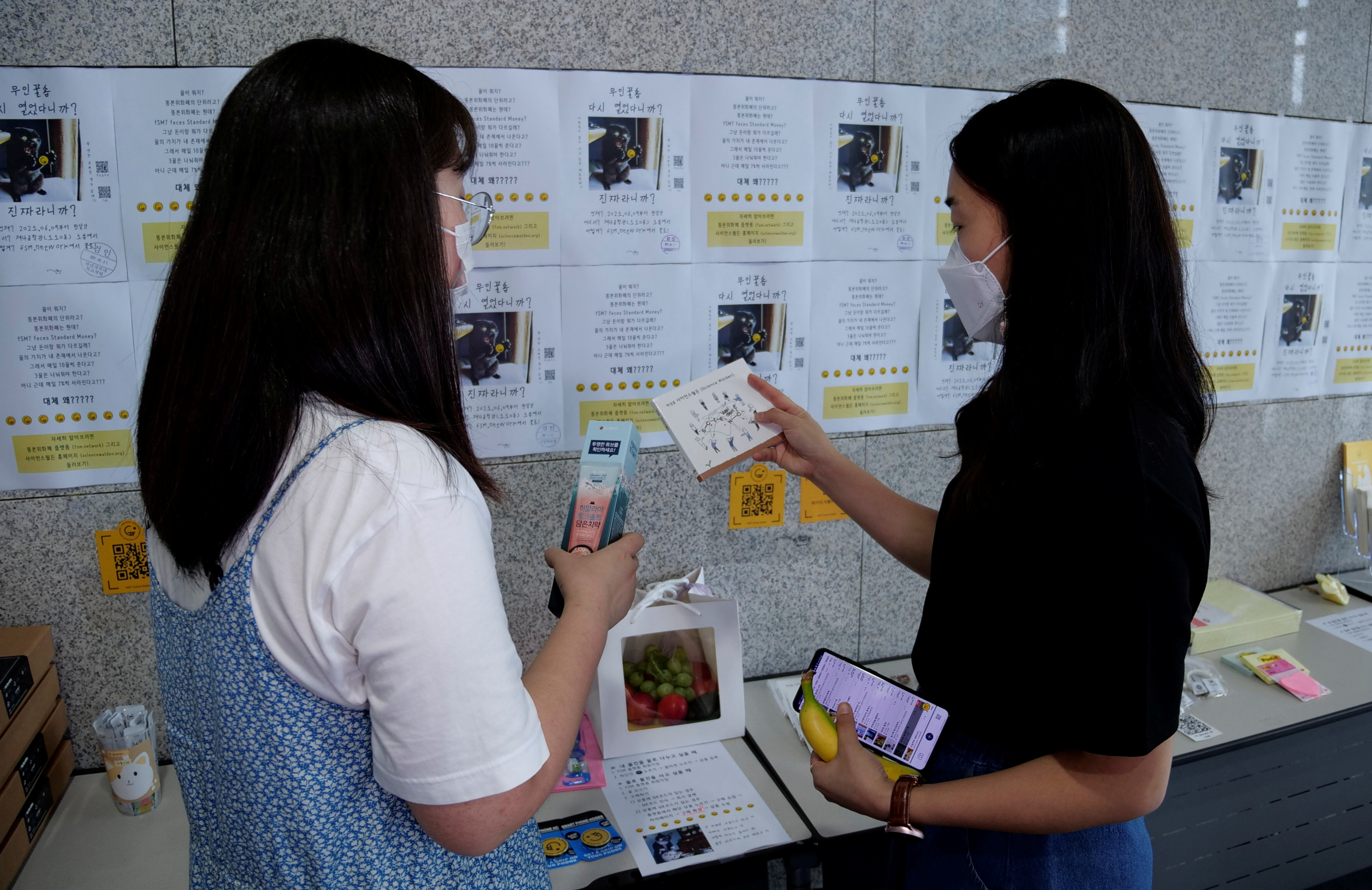 Women take a look at items at a faeces currency market at Ulsan National Institute of Science and Technology (UNIST) in Ulsan, South Korea, July 6, 2021. Picture taken on July 6, 2021. REUTERS/Daewoung Kim