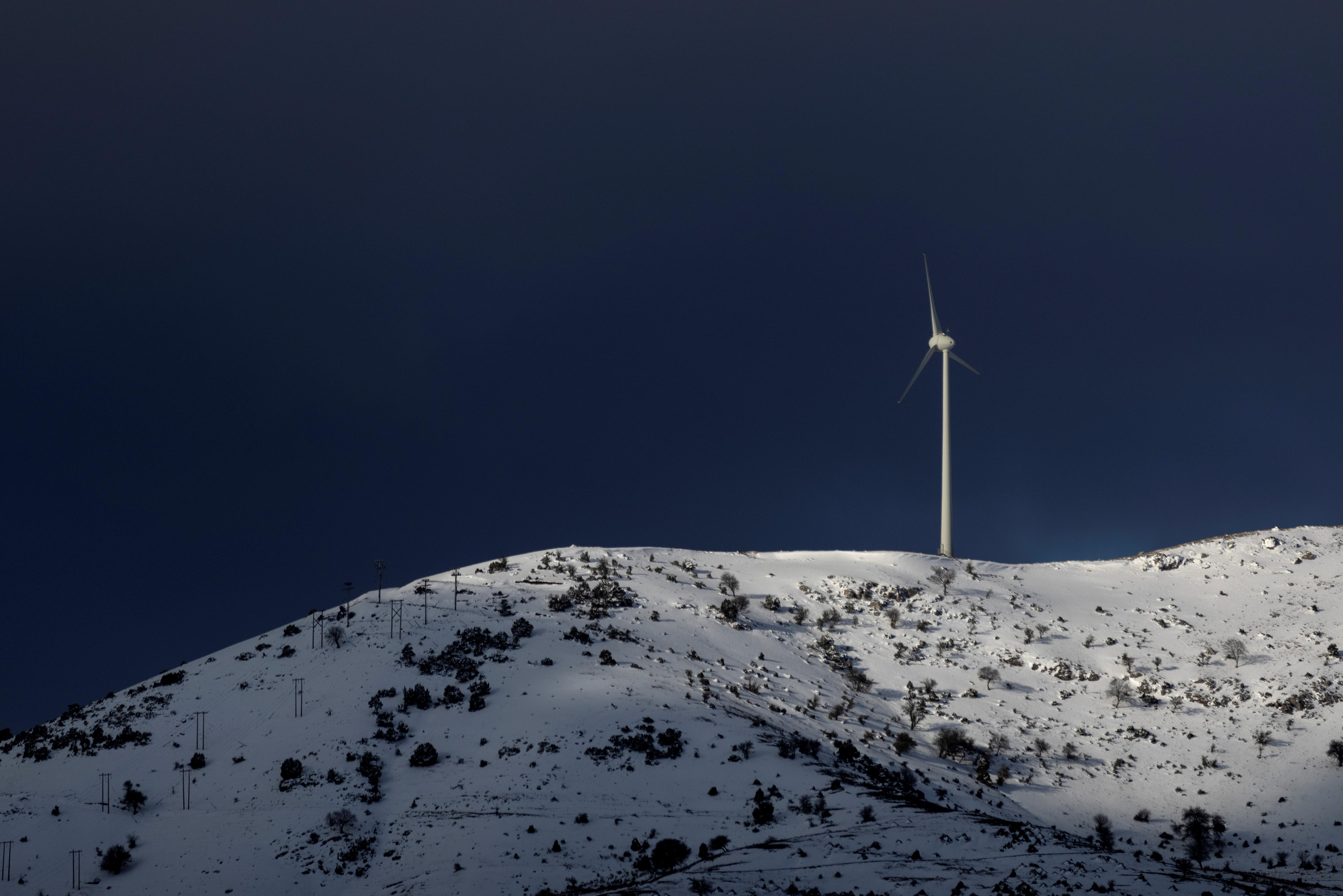 A wind turbine operates on a snowy mountain near the town of Kalavrita, Greece, March 17, 2021. REUTERS/Alkis Konstantinidis