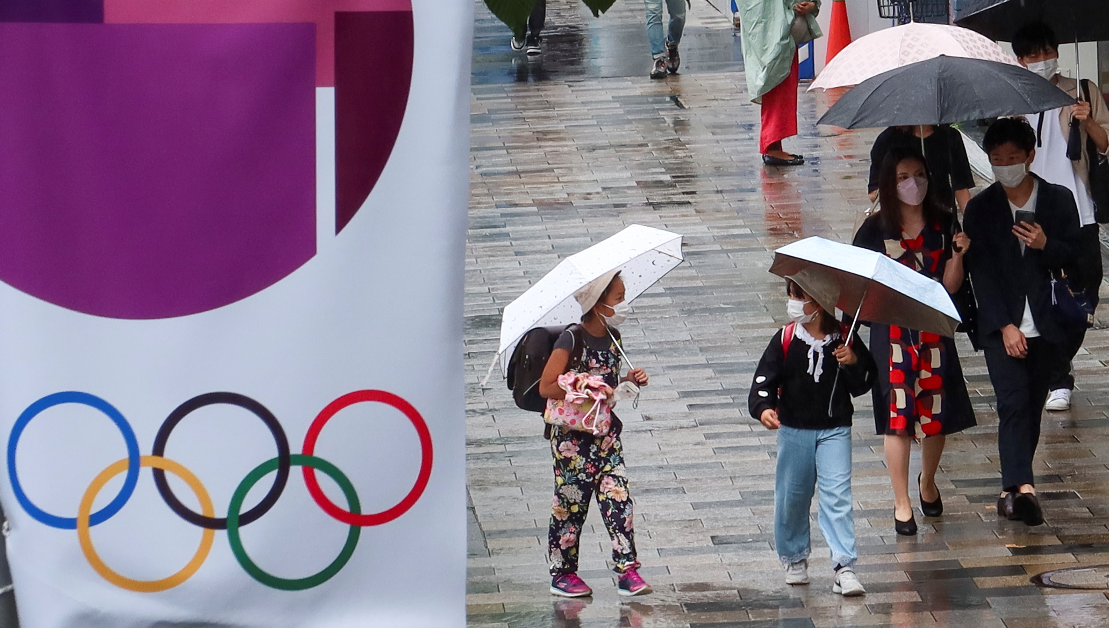 People walk on a street next to an advertisement for Tokyo 2020 Olympic and Paralympic Games, amid the coronavirus disease (COVID-19) pandemic, in Tokyo, Japan June 19, 2021. REUTERS/Pawel Kopczynski