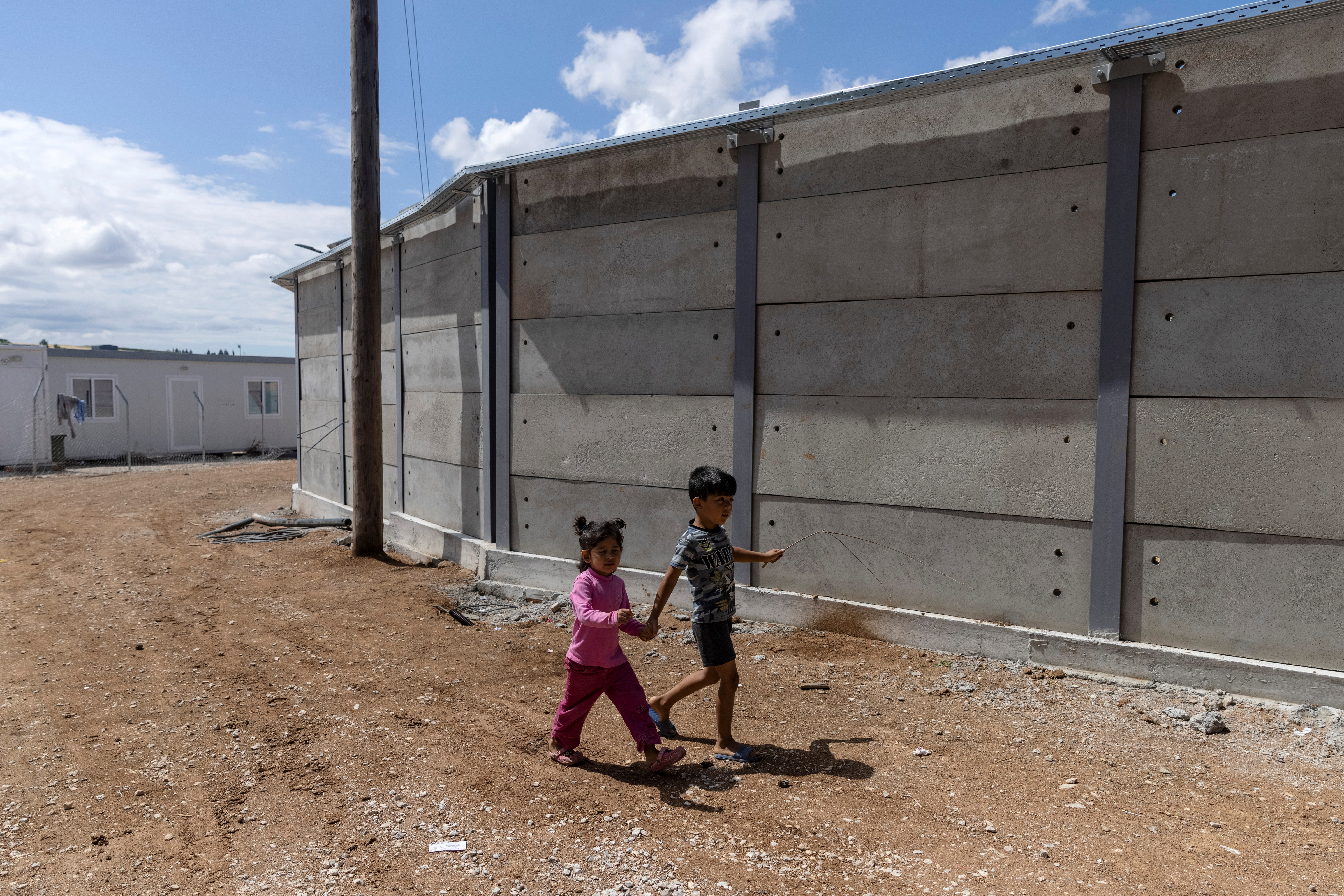 Children walk next to a newly built concrete wall inside the Ritsona camp for refugees and migrants, in Greece, June 15, 2021. REUTERS/Alkis Konstantinidis