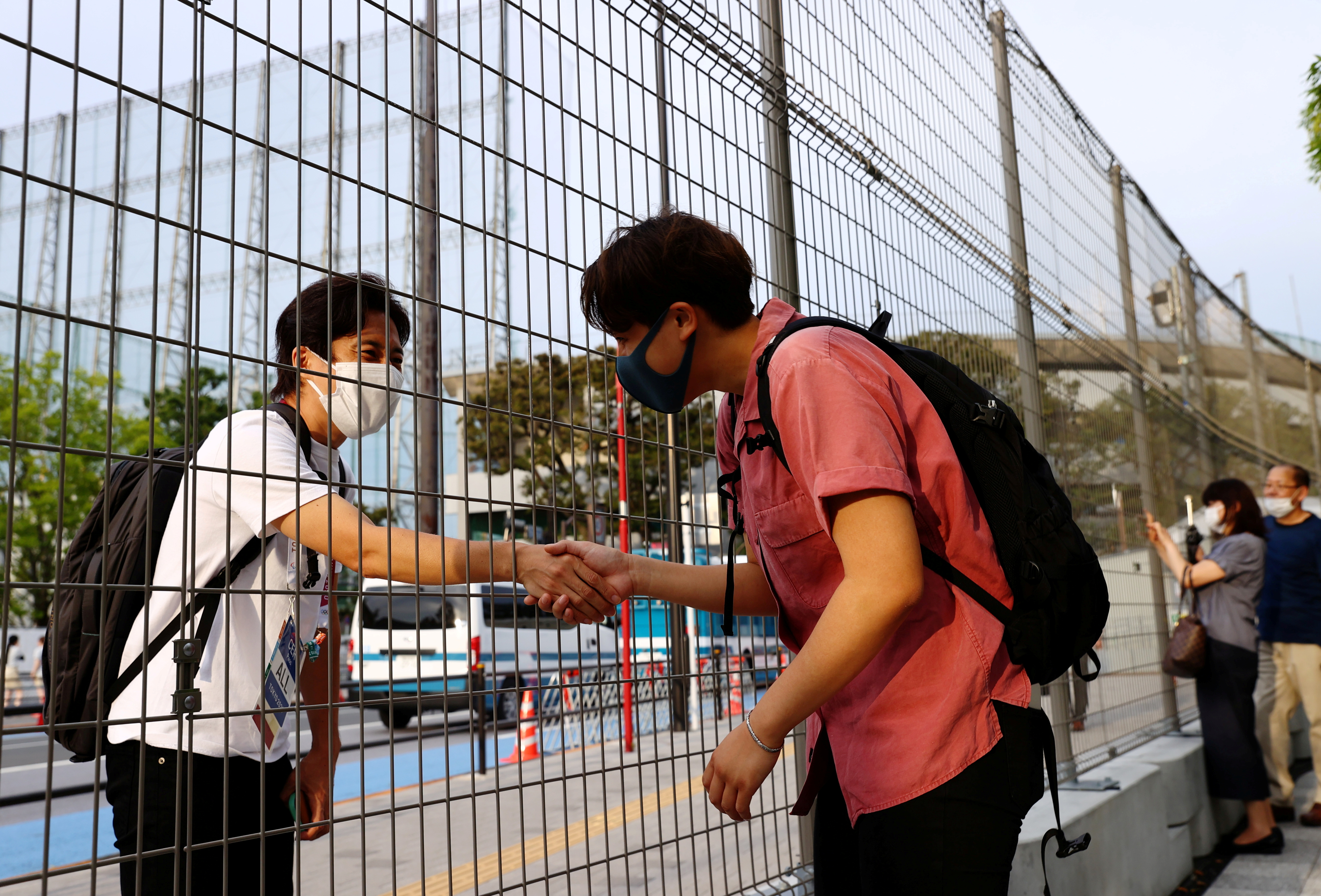 Arisa Tsubata, a nurse and a boxer, shakes hands with a staff member of the opening and closing ceremony of the Tokyo 2020 Olympic Games through a fence outside the National Stadium, the main venue of the Tokyo 2020 Olympic Games in Tokyo, Japan, July 26, 2021. Picture taken on July 26, 2021.   REUTERS/Kim Kyung-Hoon/File Photo