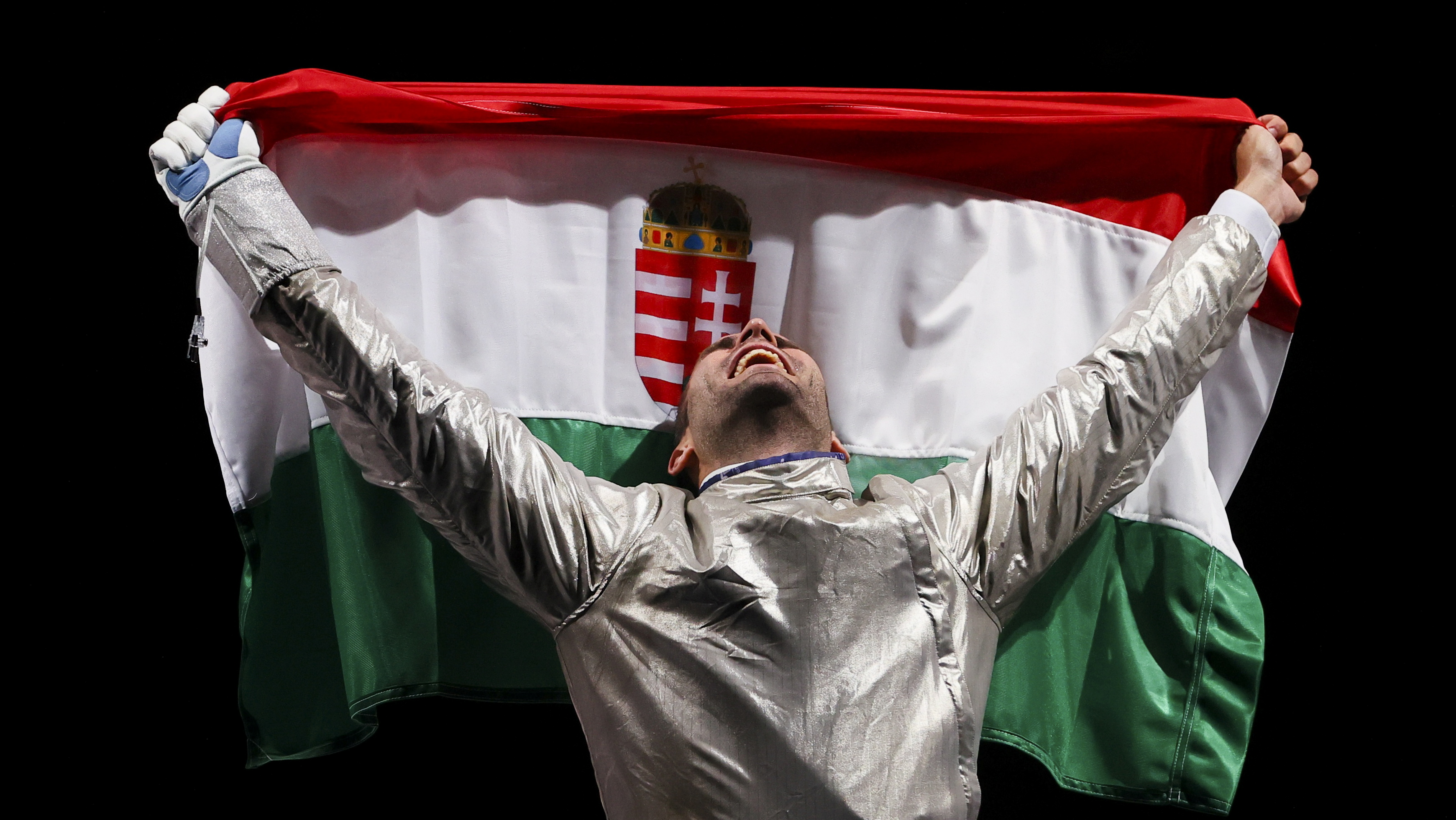 Tokyo 2020 Olympics - Fencing - Men's Individual Sabre - Gold medal match - Makuhari Messe Hall B - Chiba, Japan - July 24, 2021. Aron Szilagyi of Hungary celebrates winning gold as he holds the flag of Hungary REUTERS/Maxim Shemetov