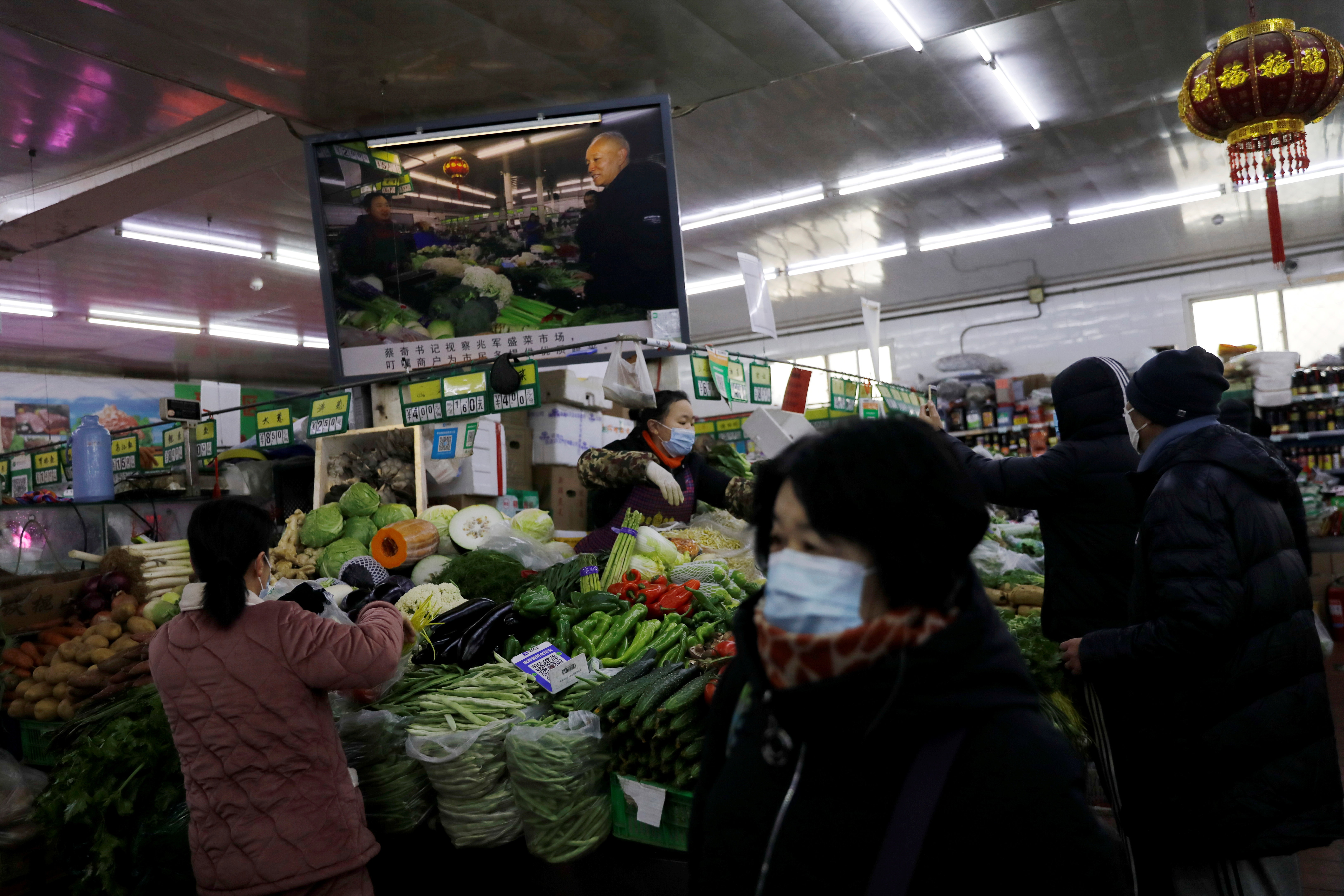 People wearing face masks following the coronavirus disease (COVID-19) outbreak shop for vegetables at a market in Beijing, China January 15, 2021. REUTERS/Tingshu Wang