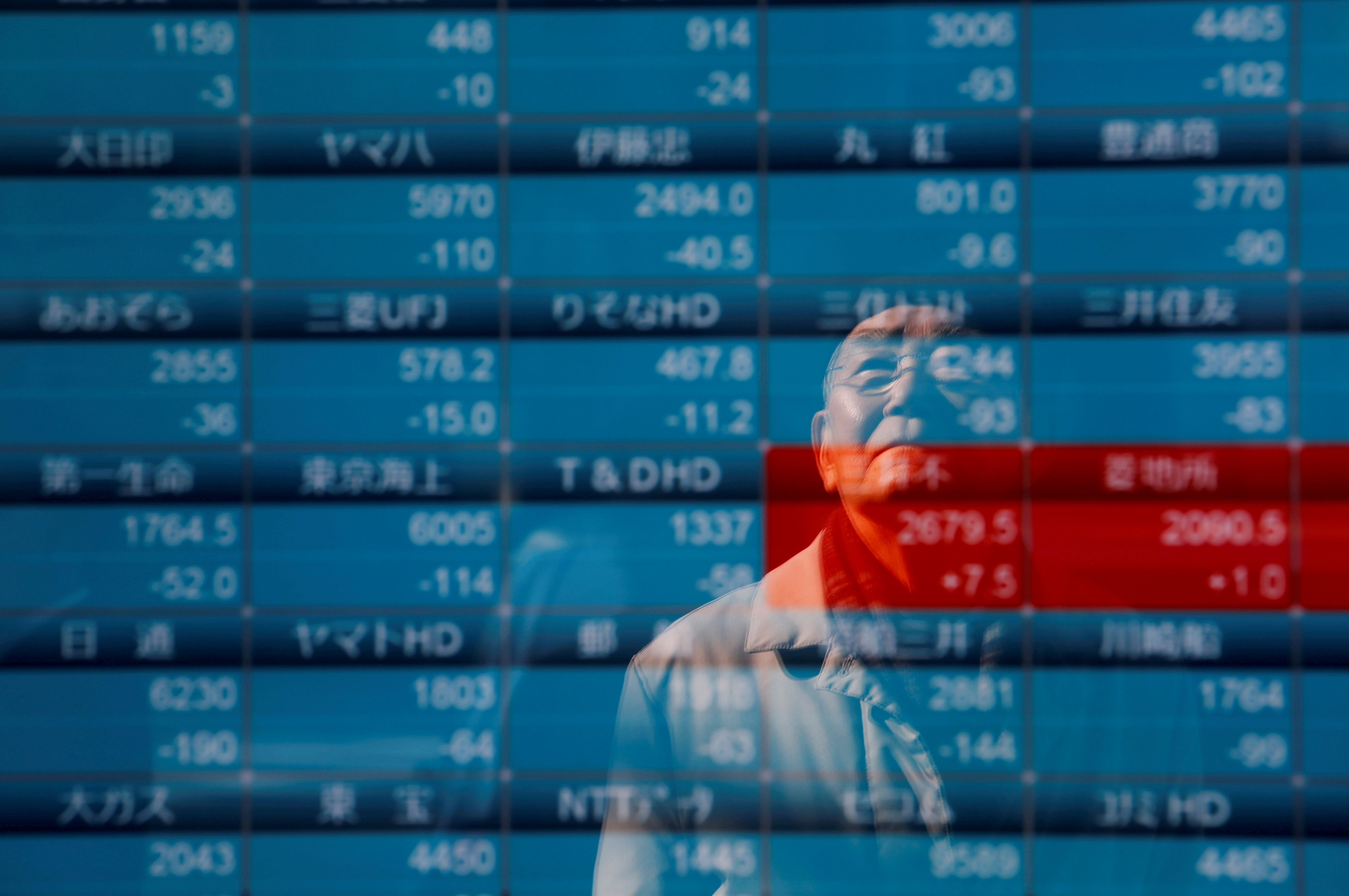 A man is reflected on a board showing stock prices outside a brokerage in Tokyo, Japan, January 6, 2020. REUTERS/Kim Kyung-Hoon/File Photo