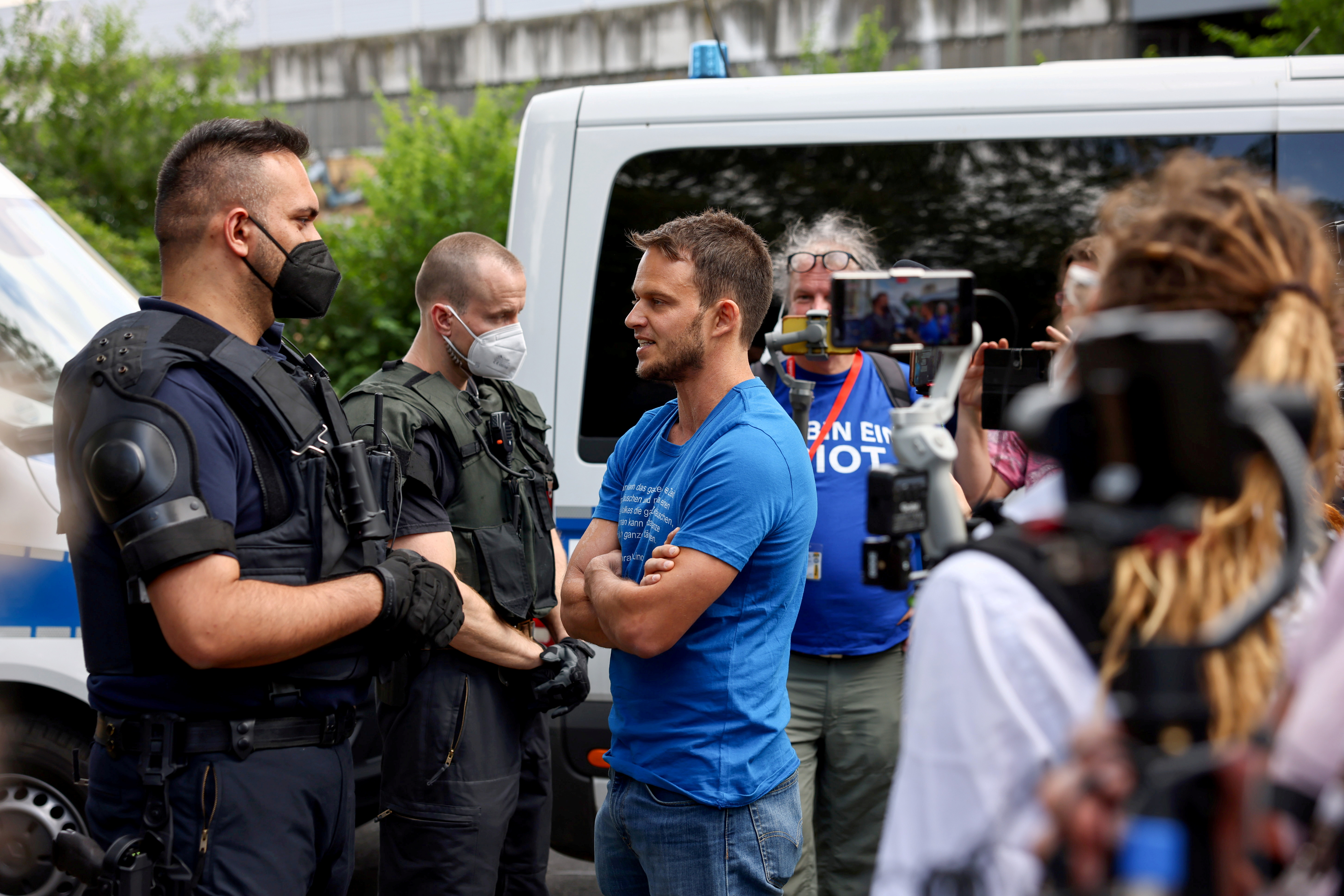 Markus Haintz, a lawyer with the Querdenken group, speaks with police officers during a protest against the government measures to curb the spread of the coronavirus disease (COVID-19), in Berlin, Germany, July 31, 2021. REUTERS/Christian Mang