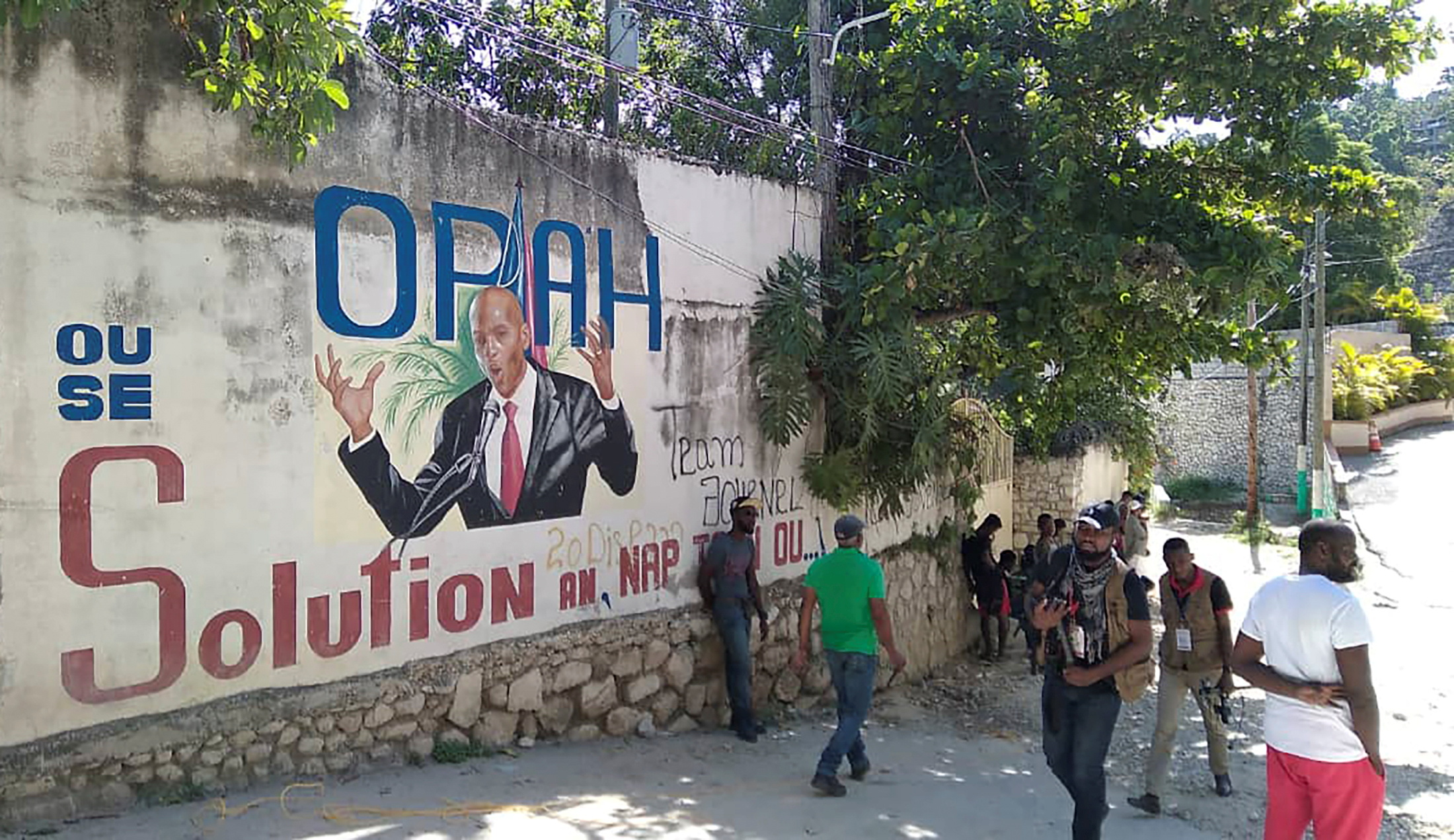 People walk past a wall with a mural depicting Haiti's President Jovenel Moise, after he was shot dead by unidentified attackers in his private residence, in Port-au-Prince, Haiti July 7, 2021. REUTERS/Robenson Sanon