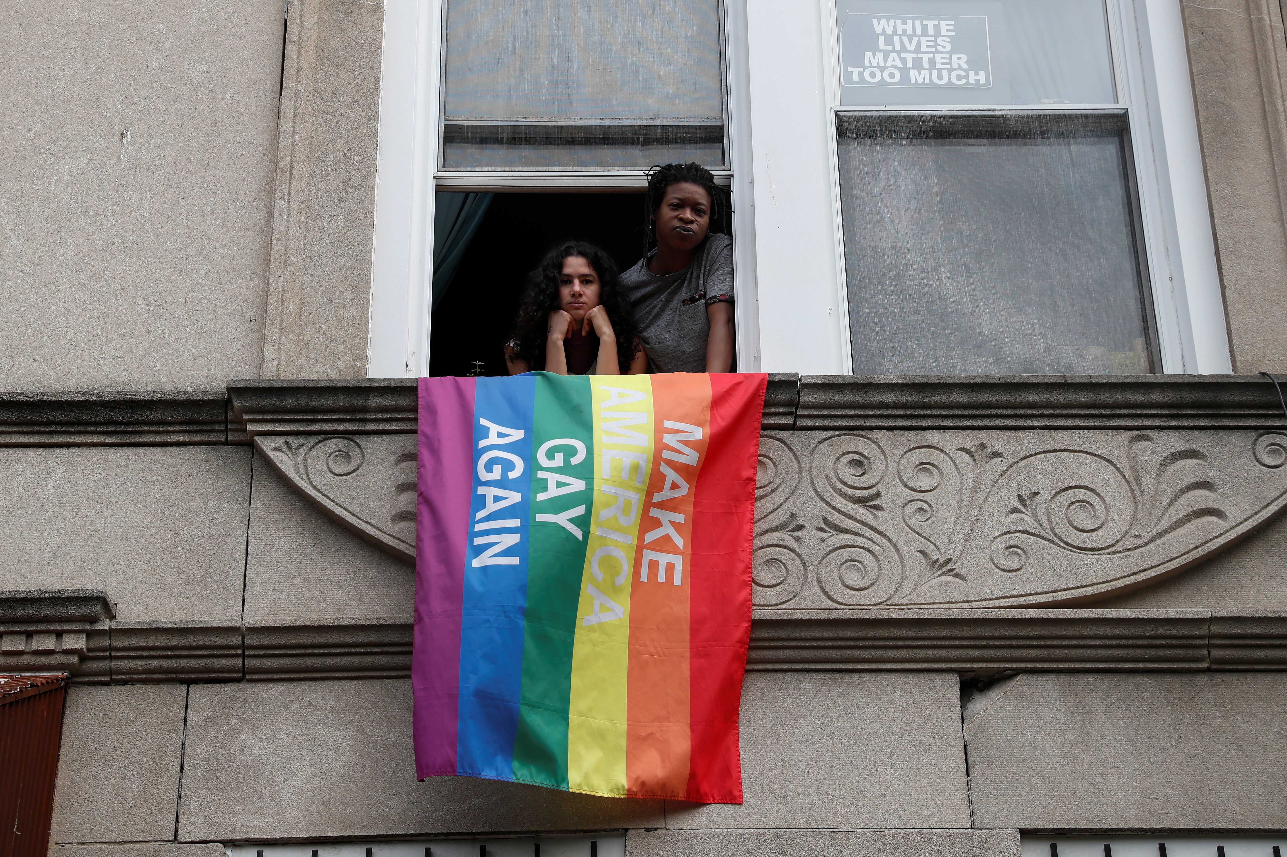 Elsa Eli Waithe and Ada Reso, 'Slavers of New York' campaign co-founders, pose at a window sill in the Bedford-Stuyvesant section of the Brooklyn borough of New York City, U.S., May 24, 2021. REUTERS/Shannon Stapleton