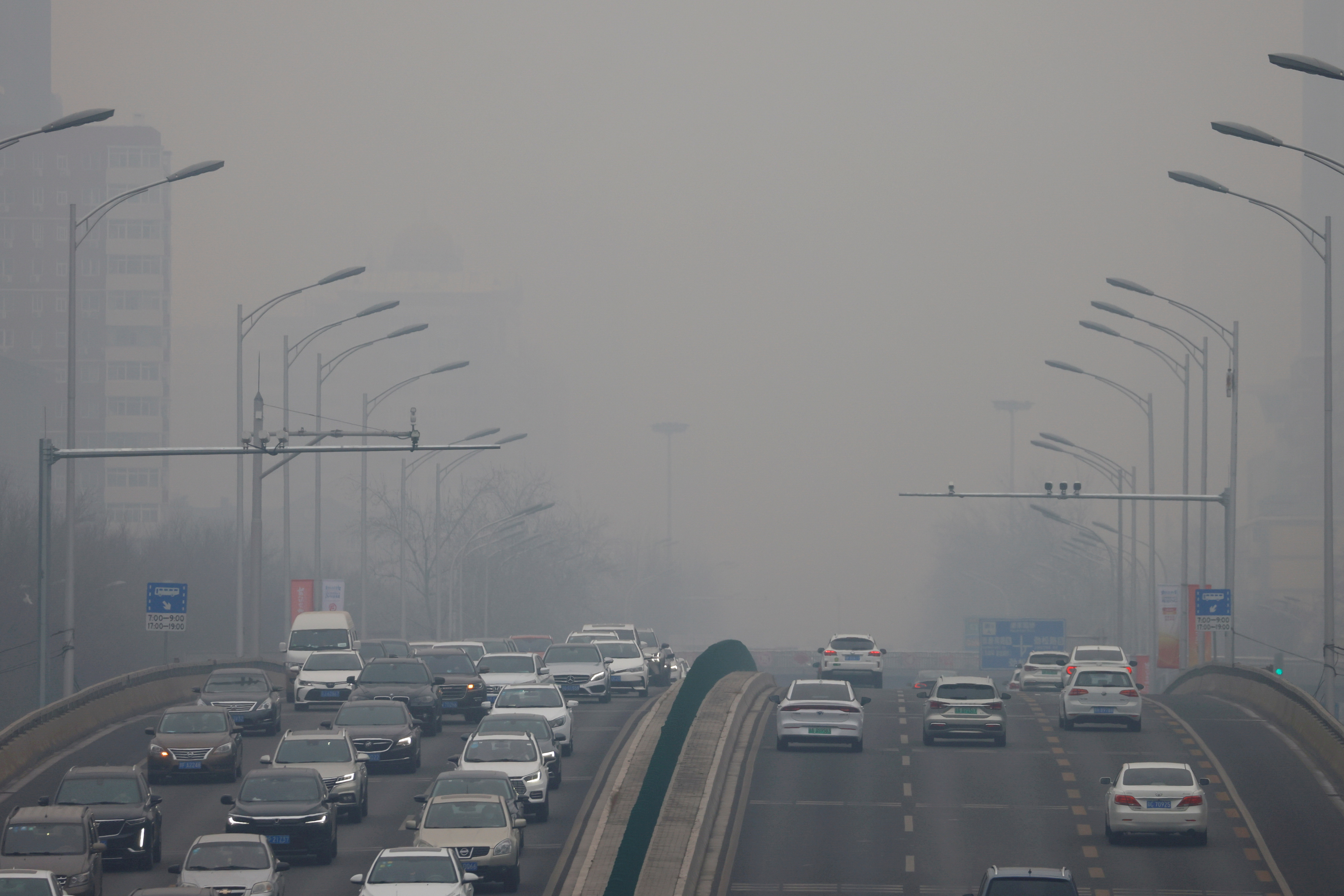 Cars move on a road during a day with polluted air in Beijing, China February 13, 2021. REUTERS/Carlos Garcia Rawlins/File Photo