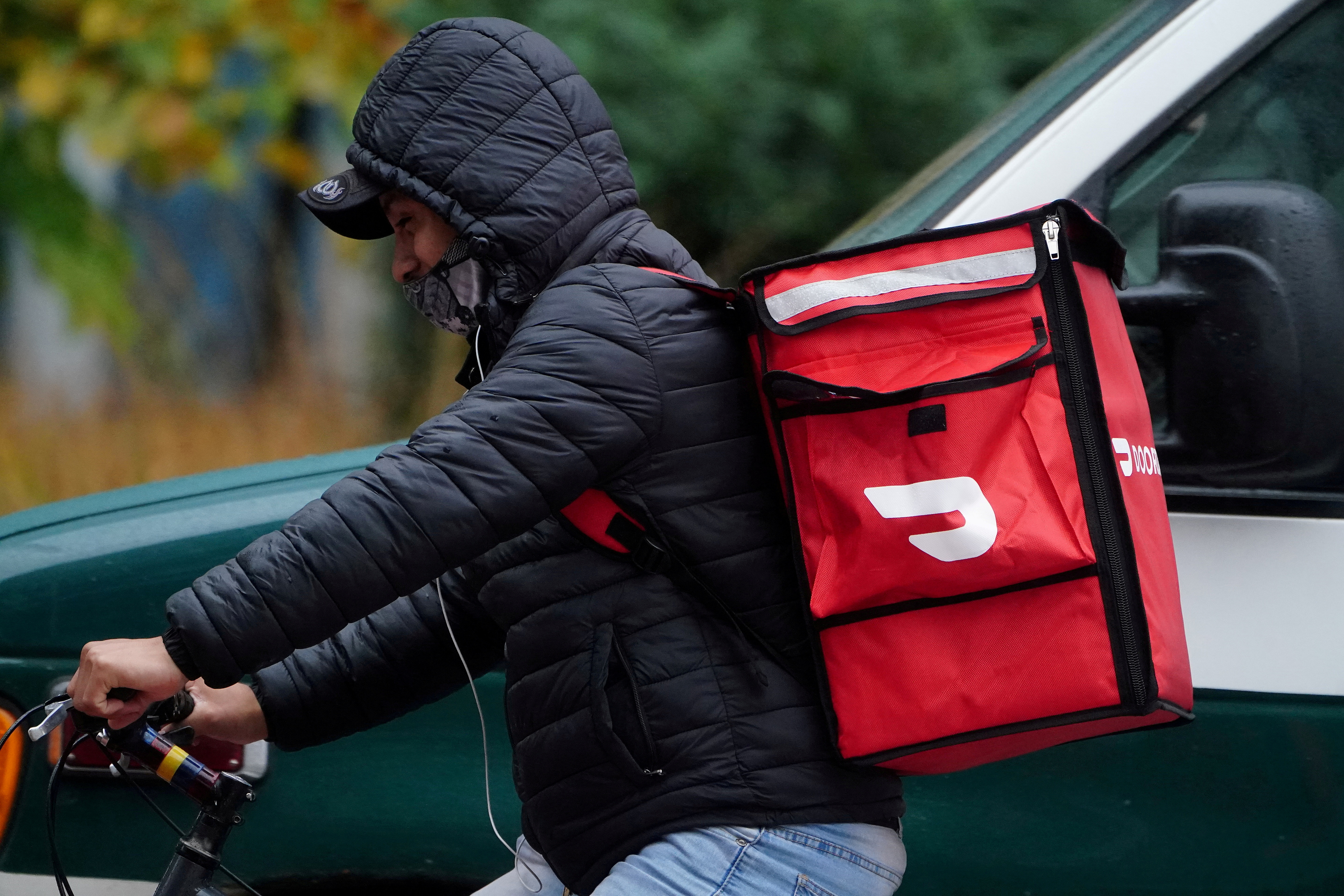 A delivery person for Doordash rides his bike in the rain during the coronavirus disease (COVID-19) pandemic in the Manhattan borough of New York City, New York, U.S., November 13, 2020. REUTERS/Carlo Allegri/File Photo