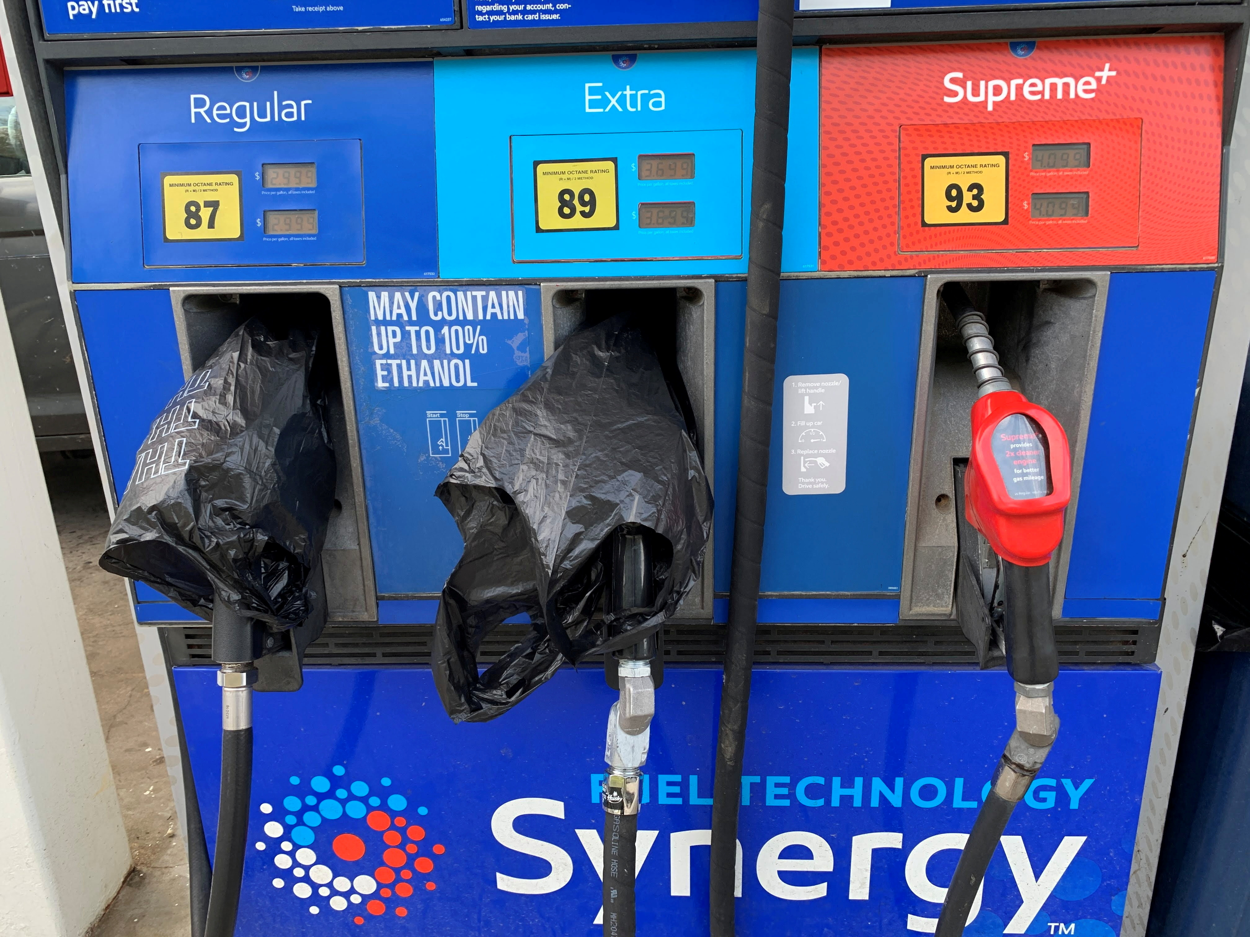 Two out of service fuel nozzles are covered in plastic on a gas pump at a gas station in Waynesville, North Carolina, after a gasoline supply crunch caused by the Colonial Pipeline hack, May 11, 2021. Martin Brossman via REUTERS