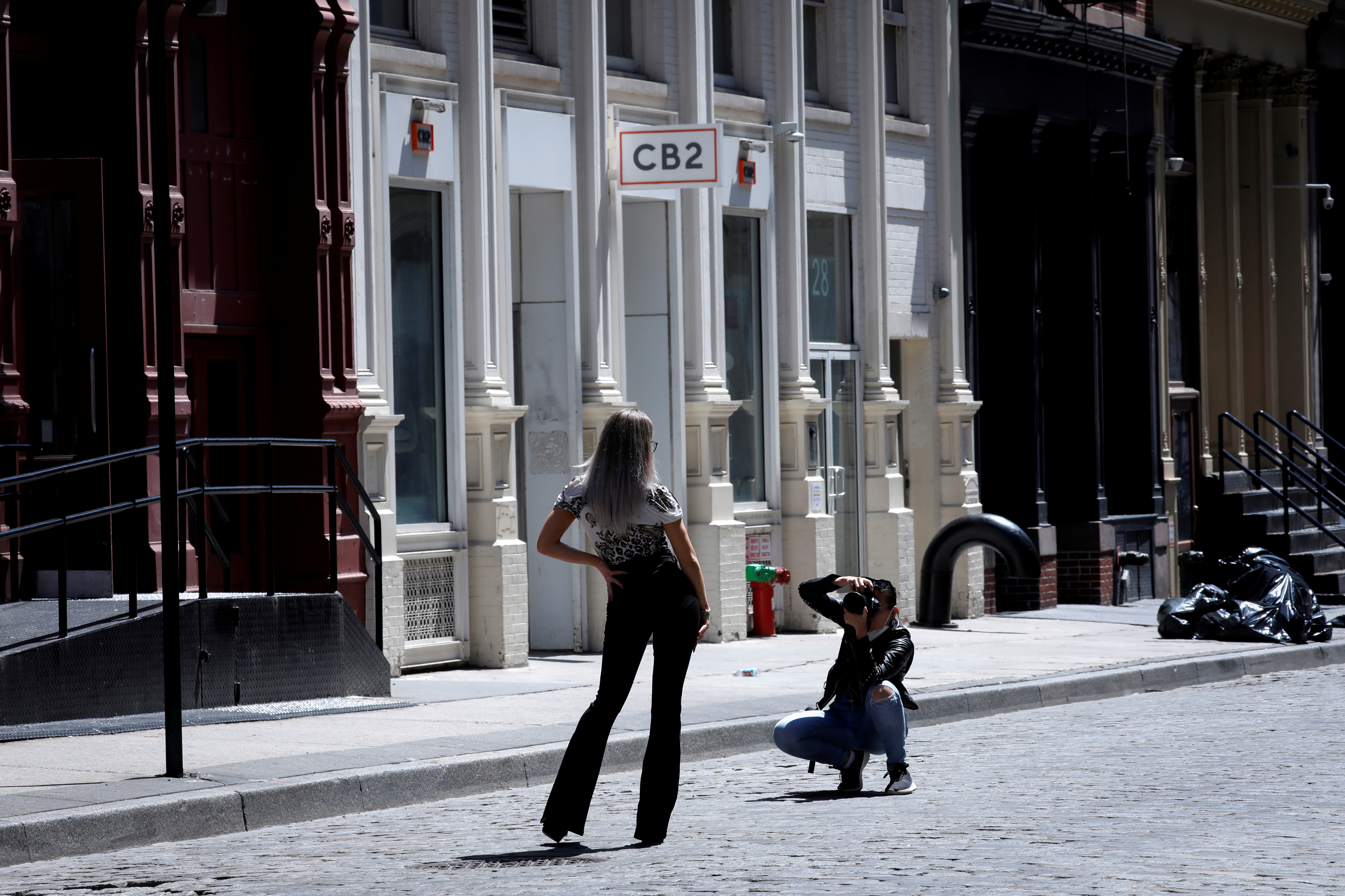 A model poses for a photographer on an empty street in front of closed shops in Soho in Manhattan during the outbreak of the coronavirus disease (COVID-19) in New York City, New York, U.S., May 26, 2020. REUTERS/Mike Segar