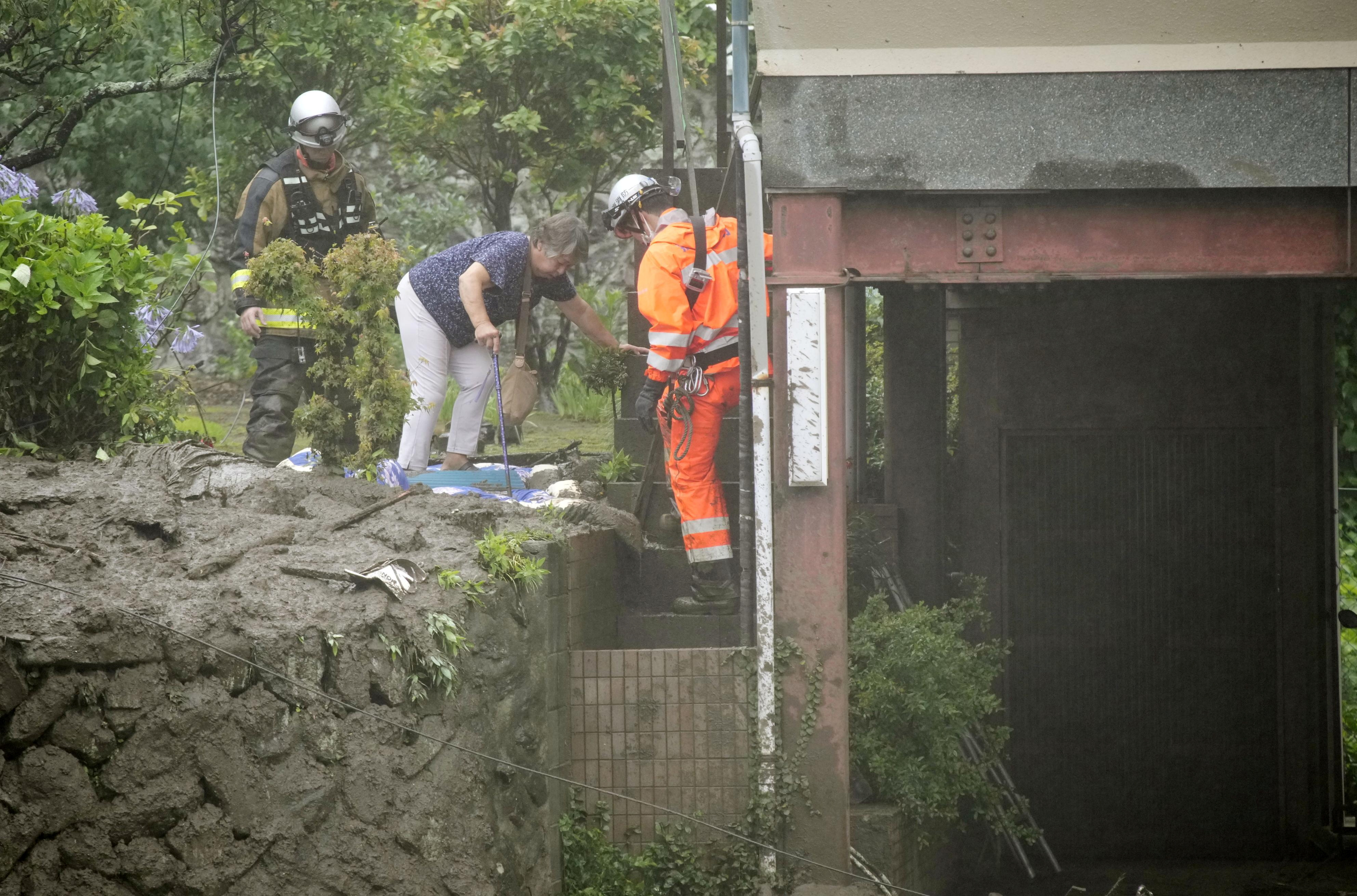 Rescue workers help a resident evacuate from a mudslide site following heavy rain at Izusan district in Atami, Japan July 3, 2021. Kyodo/via REUTERS