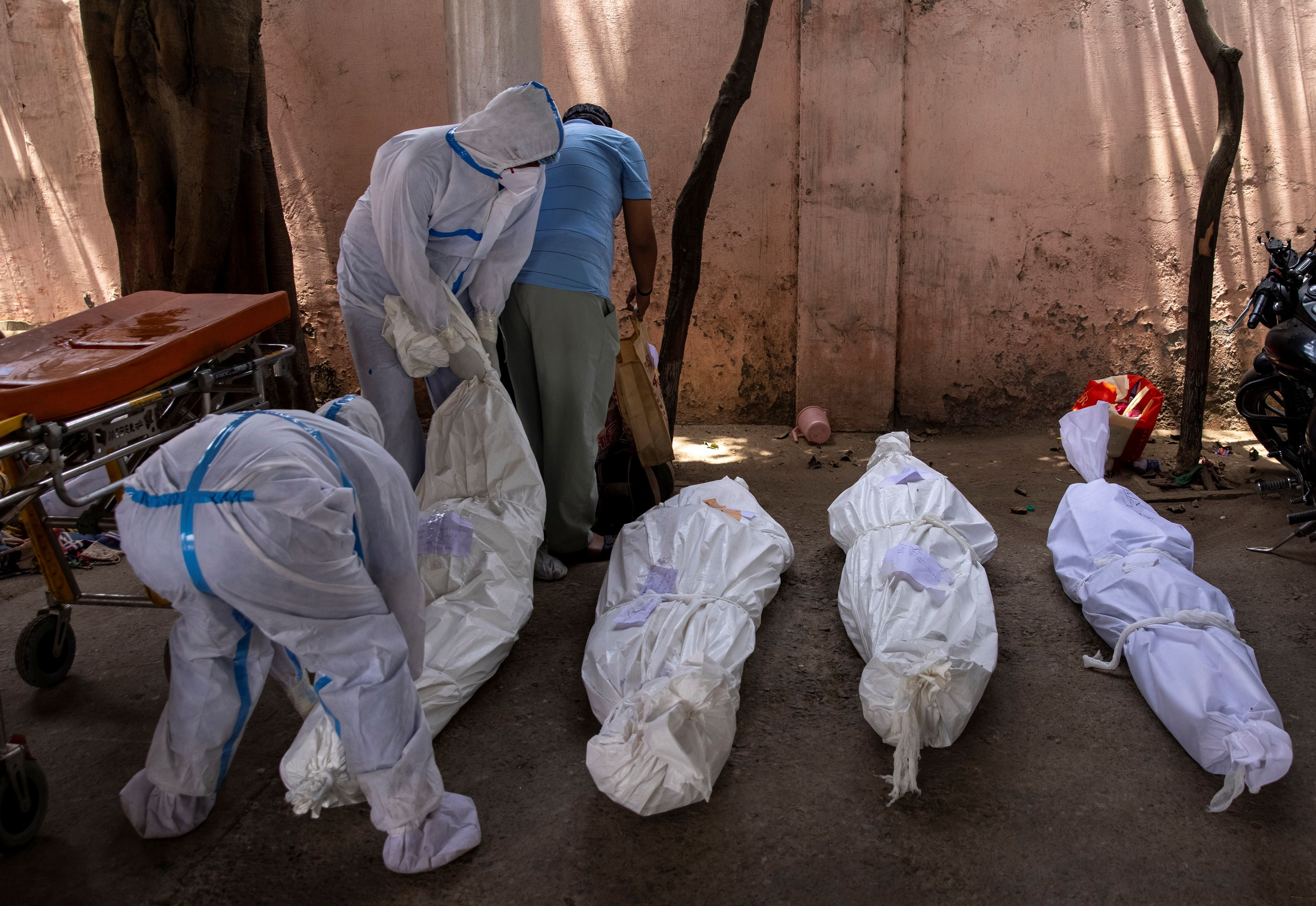 Healthcare workers place the body of a person, who died due to the coronavirus disease (COVID-19), on the ground for cremation at a crematorium ground in New Delhi, India, April 28, 2021. REUTERS/Danish Siddiqui