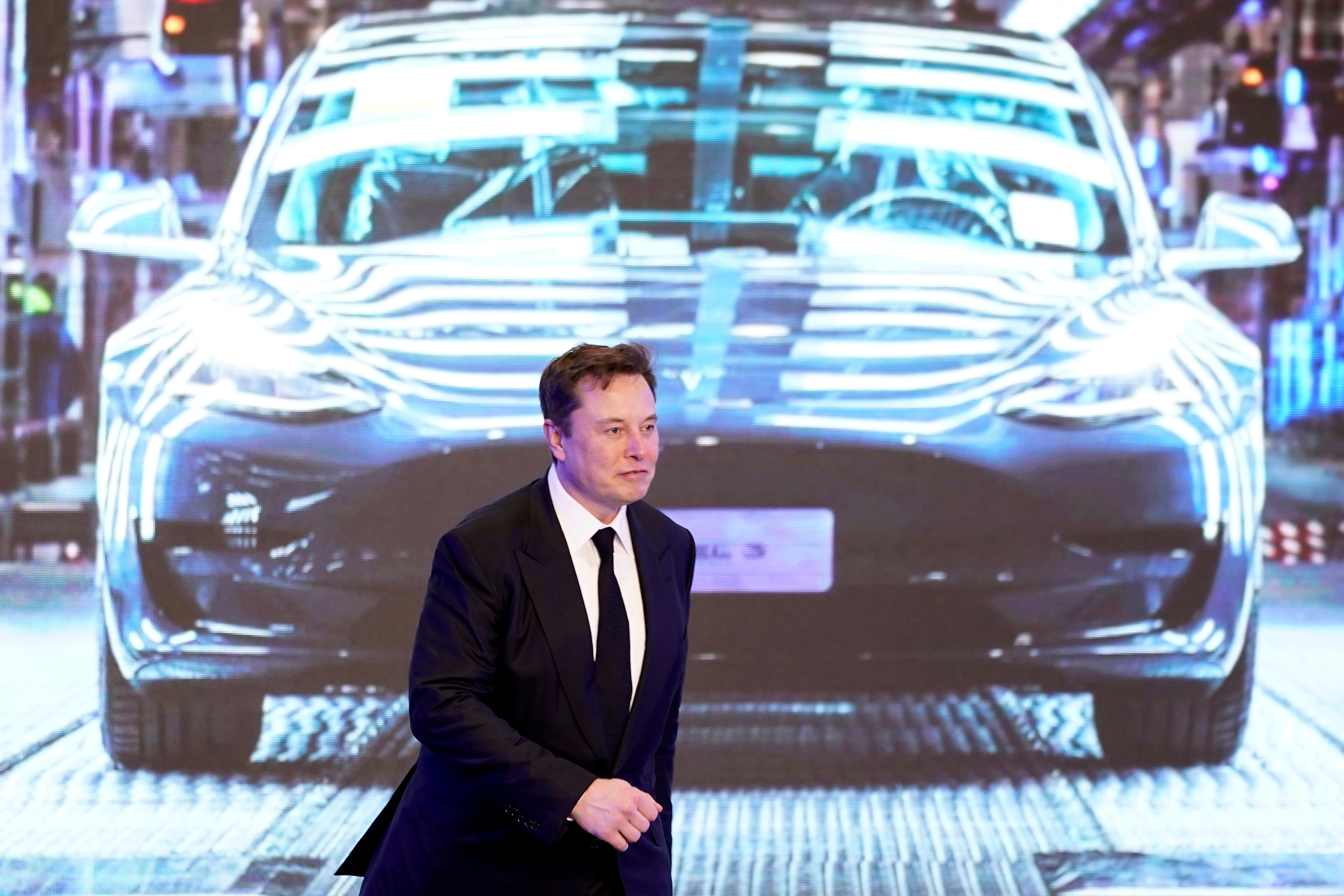Tesla Inc CEO Elon Musk walks next to a screen showing an image of Tesla Model 3 car during an opening ceremony for Tesla China-made Model Y program in Shanghai, China January 7, 2020. REUTERS/Aly Song/File Photo/File Photo