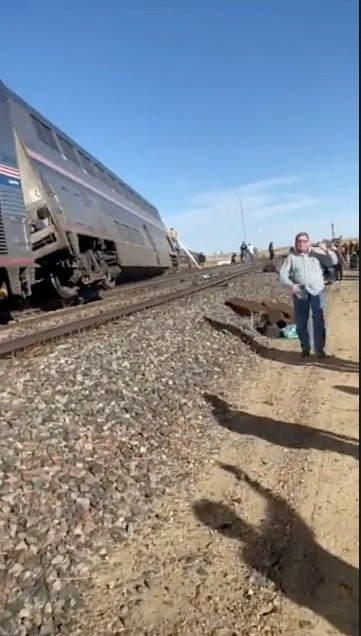 People wait at the side of train tracks at the scene of a train derailment near Havre, Montana, U.S. September 25, 2021, in this still image obtained from video. Courtesy of  Jacob Cordeiro / Social Media via REUTERS