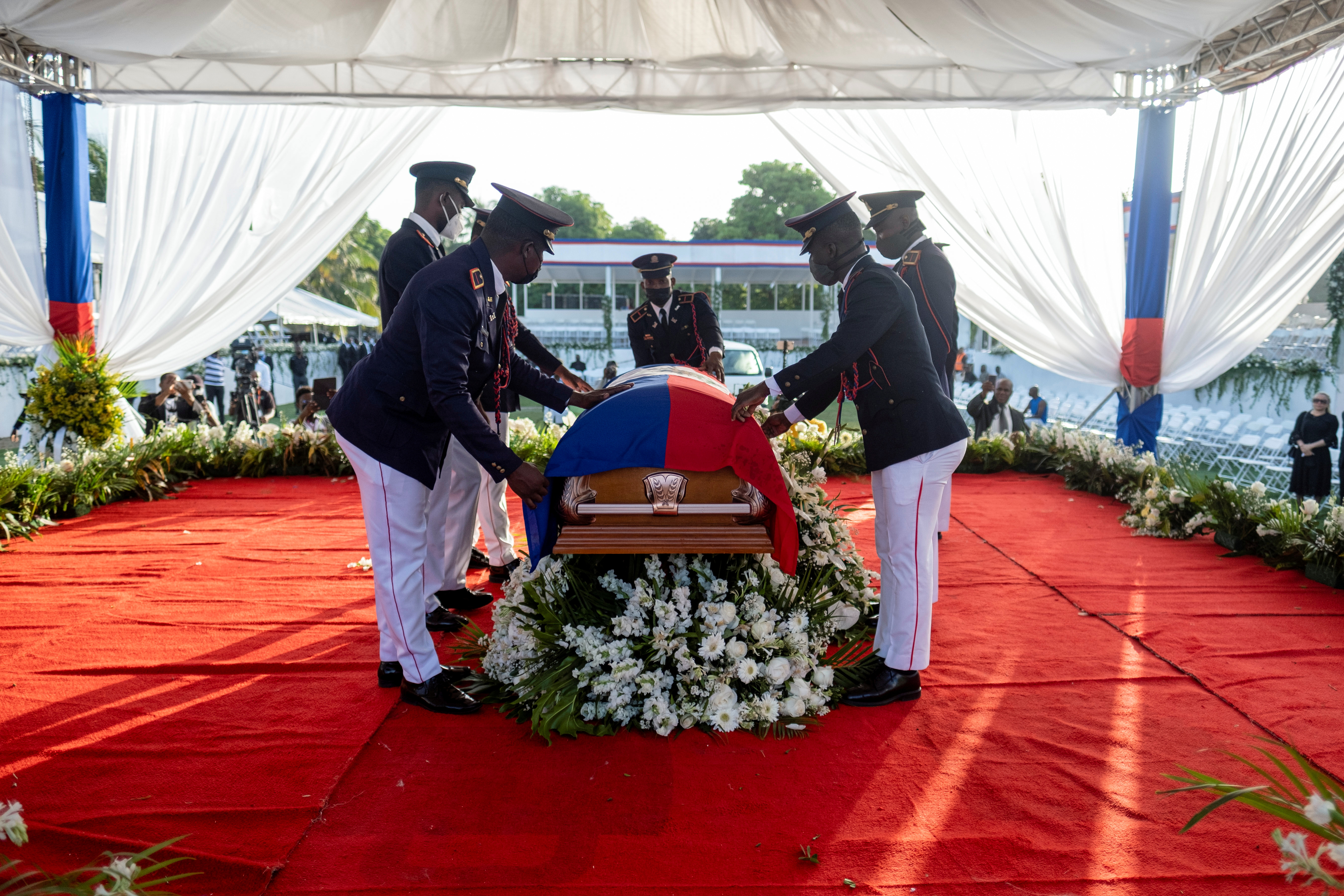 Presidential honor guards place a national flag over the coffin of late Haitian President Jovenel Moise, who was shot dead earlier this month, during the funeral at his family home in Cap-Haitien, Haiti, July 23, 2021. REUTERS/Ricardo Arduengo