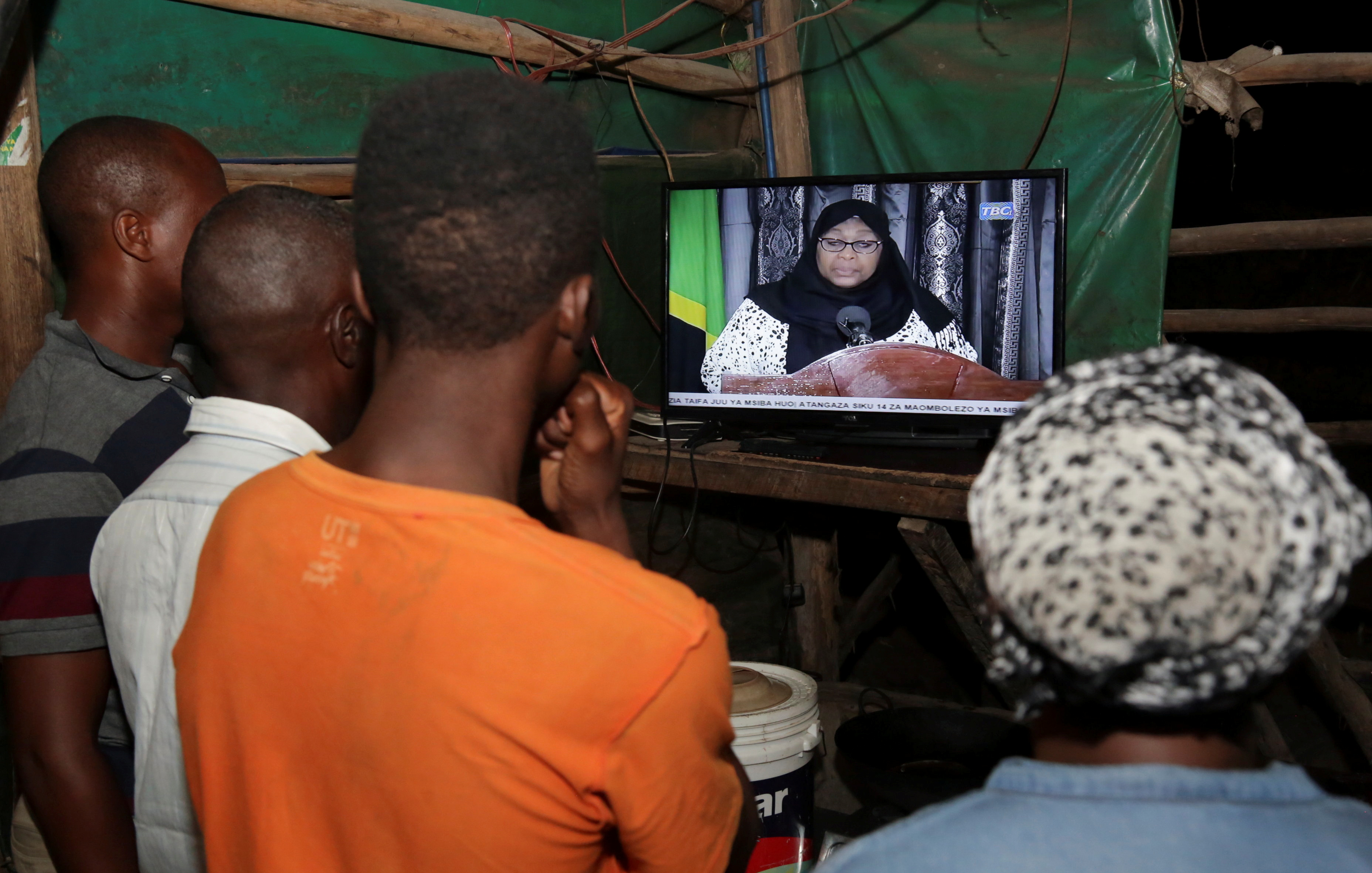Residents watch the television announcement of the death of Tanzania's President John Magufuli, addressed by Vice President Samia Suluhu Hassan in Dar es Salaam, Tanzania March 18, 2021. REUTERS/Emmanuel Herman