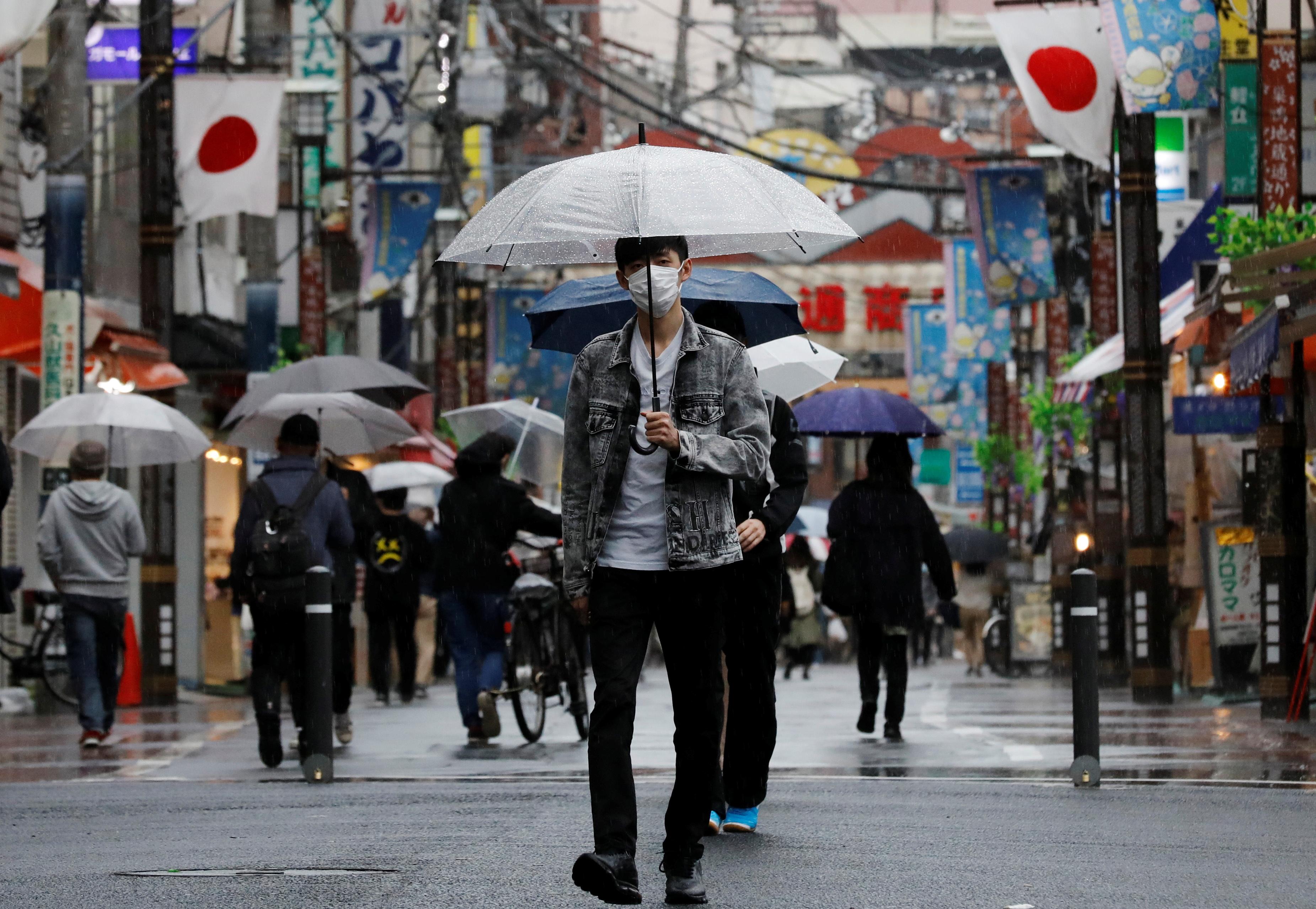 A man wearing a protective face mask, amid the coronavirus disease (COVID-19) pandemic, makes his way at a local shopping street in Tokyo, Japan, May 5, 2021. REUTERS/Kim Kyung-Hoon