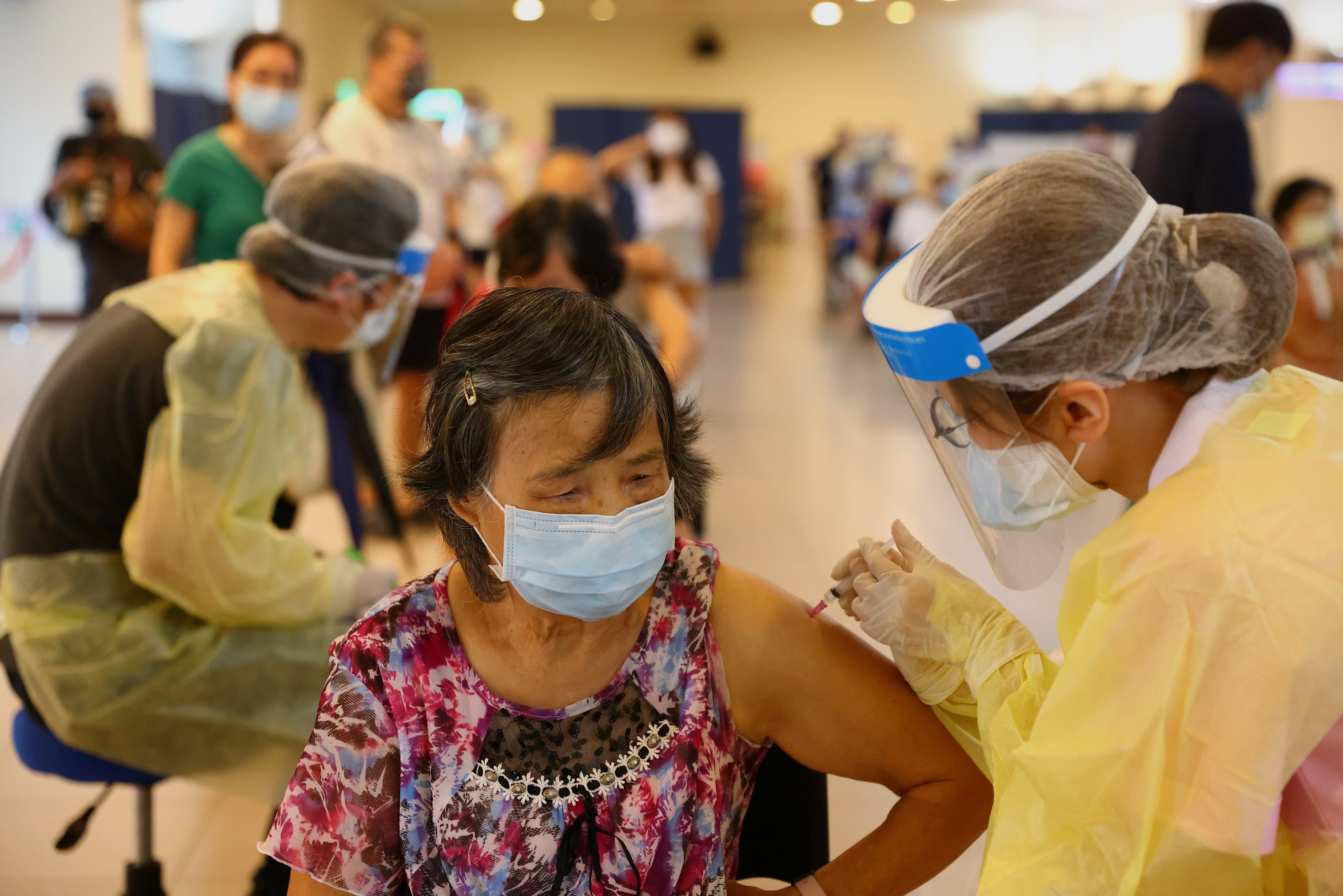 A medical worker administers a dose of the AstraZeneca vaccine against the coronavirus disease (COVID-19) to a woman during a vaccination session for elderly people over 75 years old, at a stadium in New Taipei City, Taiwan June 25, 2021. REUTERS/Ann Wang