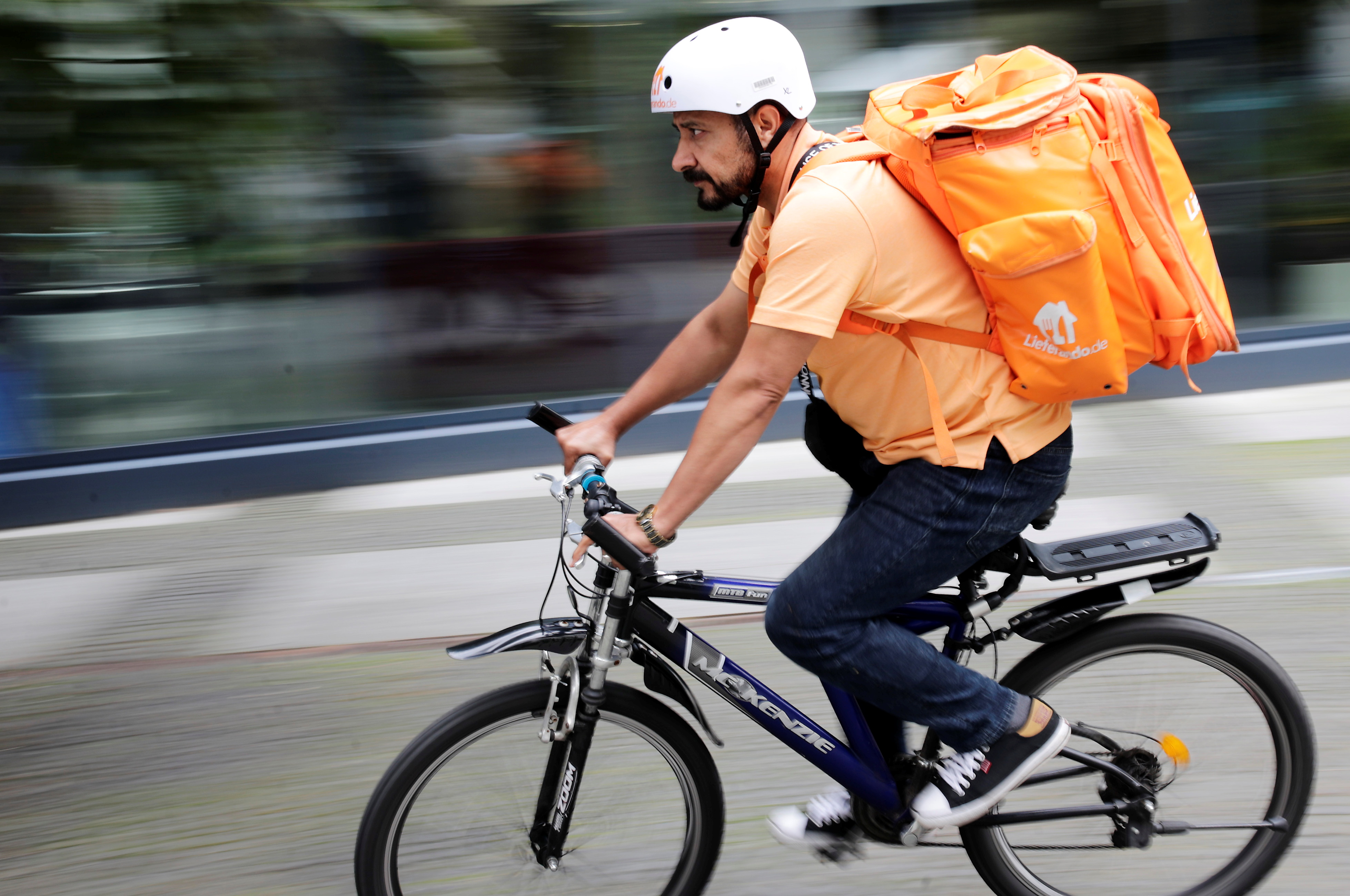 Former Afghan Communication Minister Sayed Sadaat rides a bicycle for his food delivery service job with Lieferando in Leipzig, Germany, August 26, 2021. REUTERS/Hannibal Hanschke