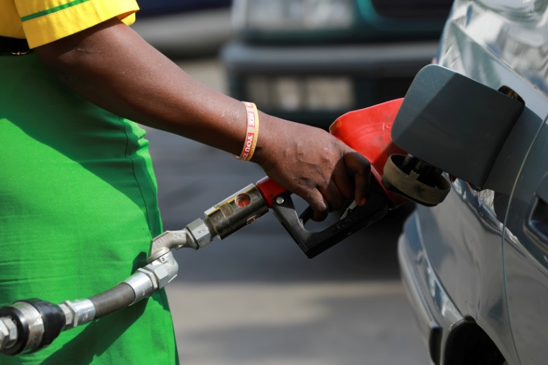 A gas station attendant pumps fuel into a customer's car at the NNPC Mega petrol station in Abuja, Nigeria March 19, 2020. REUTERS/Afolabi Sotunde/File Photo