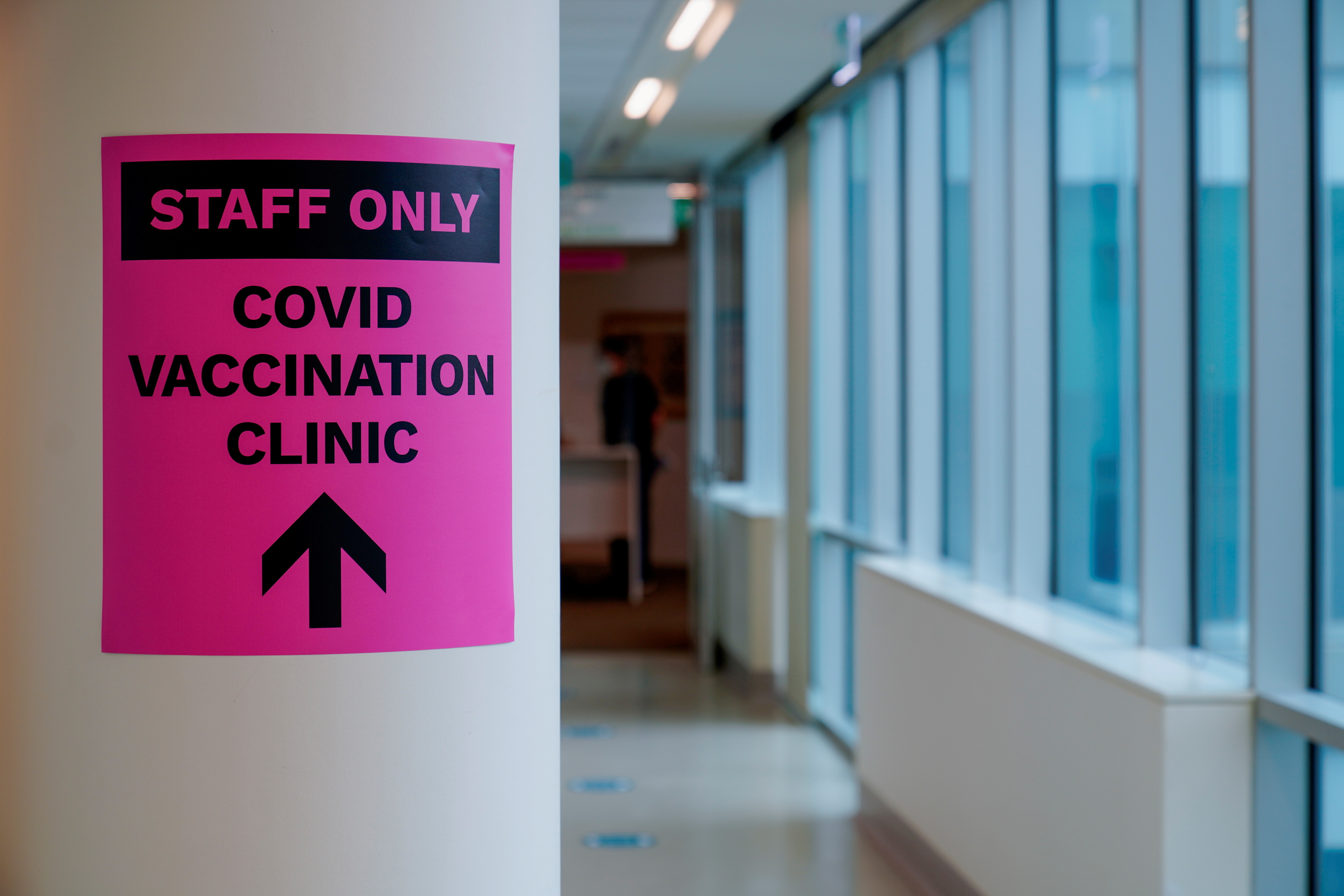 A sign for a COVID-19 vaccination clinic is seen as high-risk workers receive the first vaccines in the state of Victoria's rollout of the program, in Melbourne, Australia, February 22, 2021.  REUTERS/Sandra Sanders/File Photo