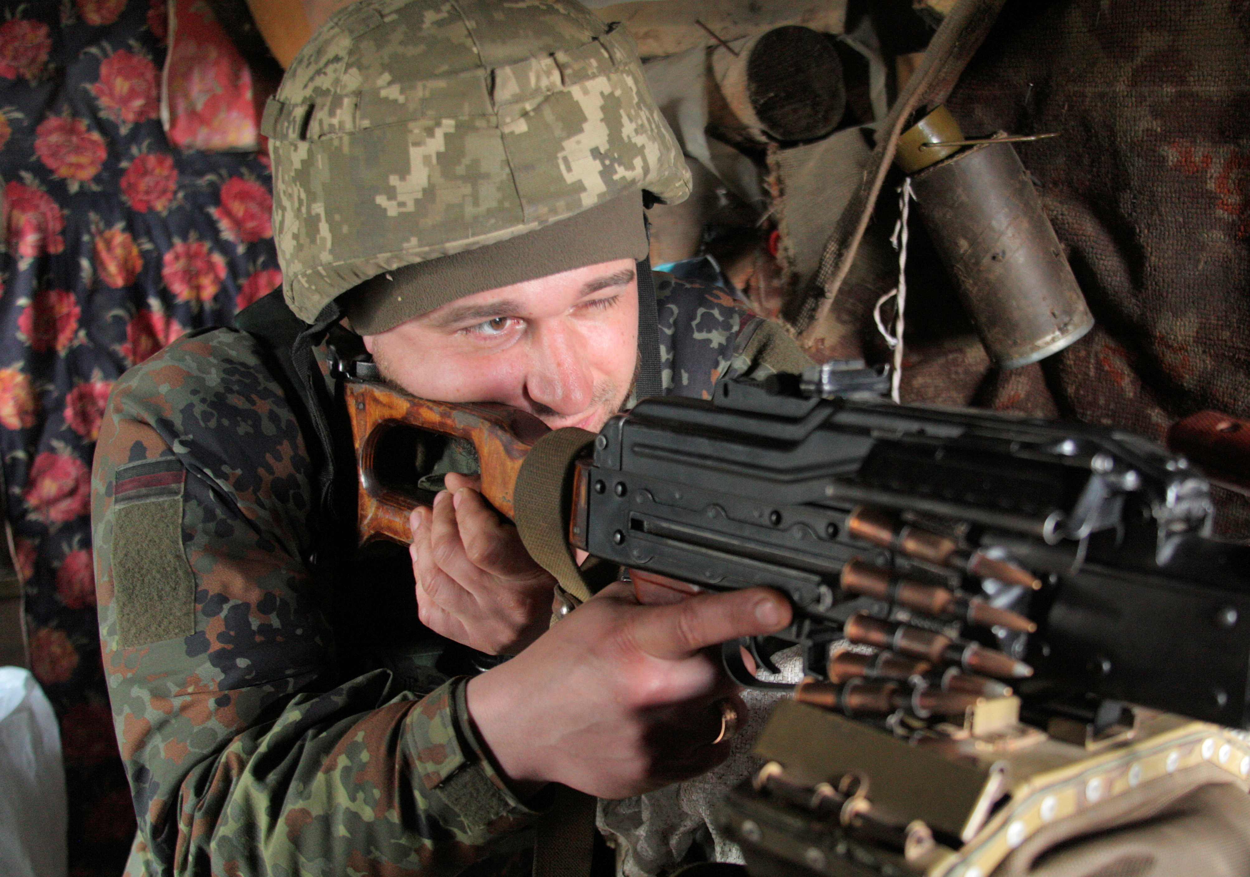 A service member of the Ukrainian armed forces points a weapon at fighting positions on the line of separation near the rebel-controlled city of Donetsk, Ukraine April 16, 2021. REUTERS/Serhiy Takhmazov/File Photo