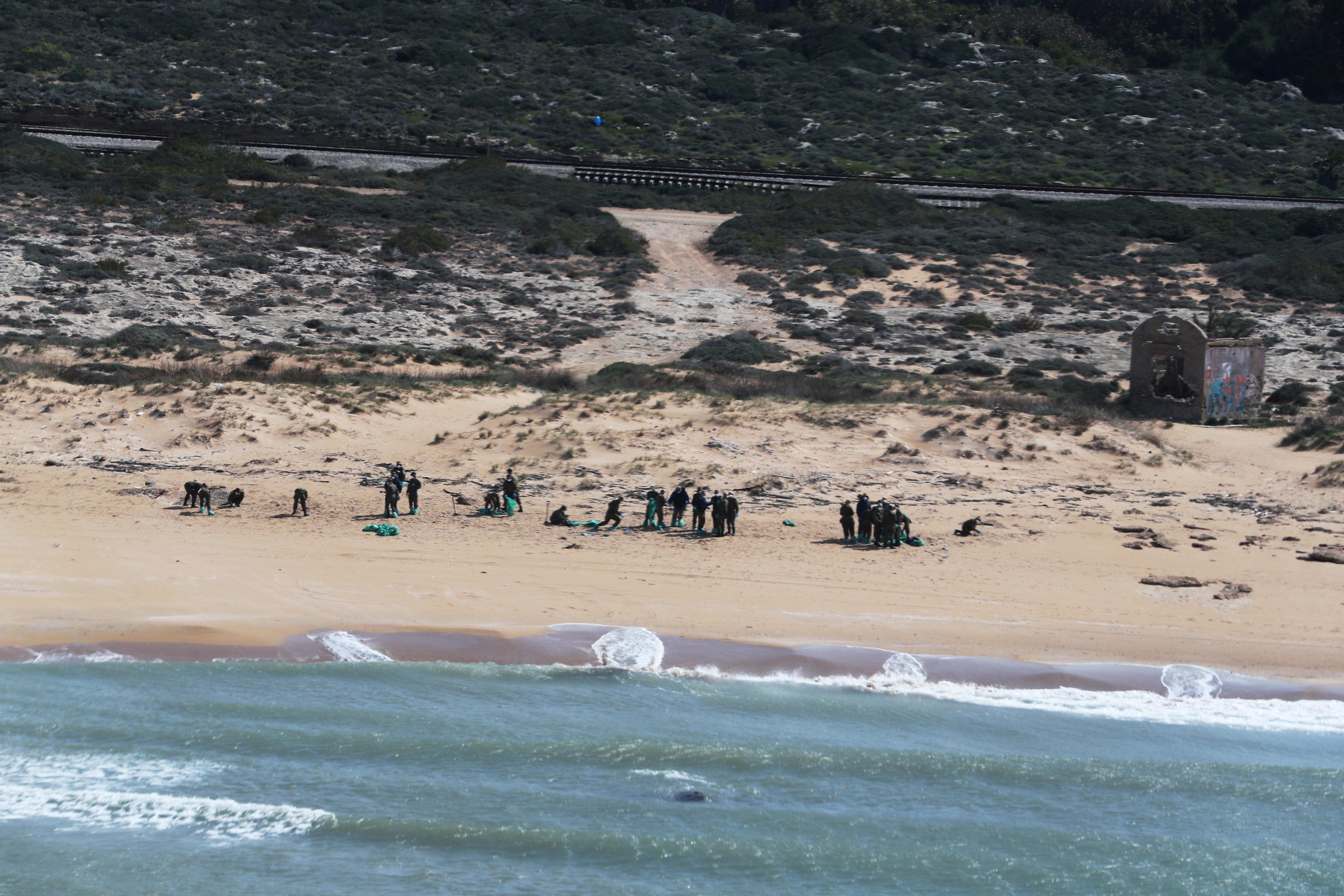 An aerial view shows Israeli soldiers cleaning tar from the sand after an offshore oil spill drenched much of Israel